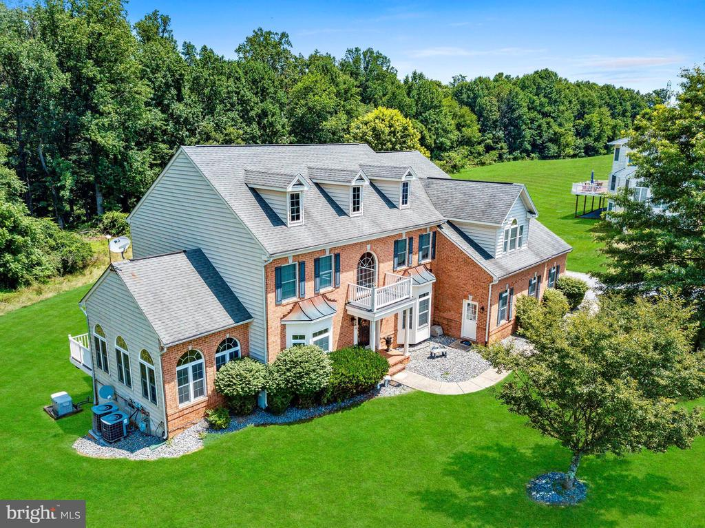 Lofty Windows; Light Filled Interiors; Gleaming Hardwood Floors; Crown Molding; Chair Railing; Cathedral Ceilings; Sleek Appliances; Island with Breakfast Bar; Ample Cabinetry; Two Story Family Room; Stone Profile Fireplace; Separate Vanities; Jetted Soaking Tub; Glass Enclosed Shower; Walk-In Closets; Design-Inspired Features Throughout; Exterior Features: Covered Front Porch, Exterior Lighting, Multiple Decks, Secure Storage, Street Lights, Backs to Trees, and Landscaped Grounds.