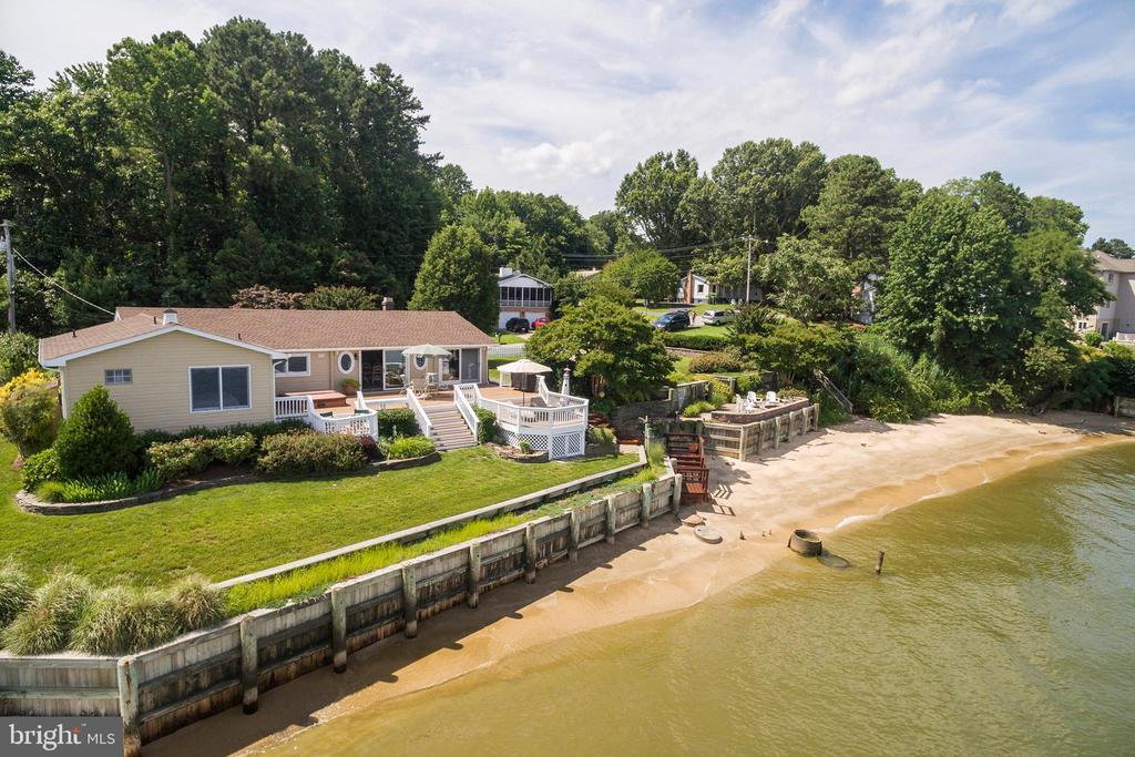 Only a few times in a lifetime are you presented with an opportunity like this one! The views are breath taking and open the windows and you will hear the waves on the Chesapeake Bay. In pristine condition with entire exterior just painted, master bath remodel, recent kitchen remodel and more.  You will be purchasing two separately deeded lots.  Two level decking with hot tub off the kitchen allows for unobstructed views. The extra lot features your owns steps leading to a sandy beach and a paver patio with firepit for the cooler months.  The perfect place for outdoor entertaining.  Irrigation is provided for the lots and lovely landscaping gives you icing on the cake!  Don't waste any time making an appointment to see this one of kind waterfront treasure because you won't be the only one to love it! Mandatory Road Maintenance Fee & covenant fee of $287 annually, part of Citizens Association.