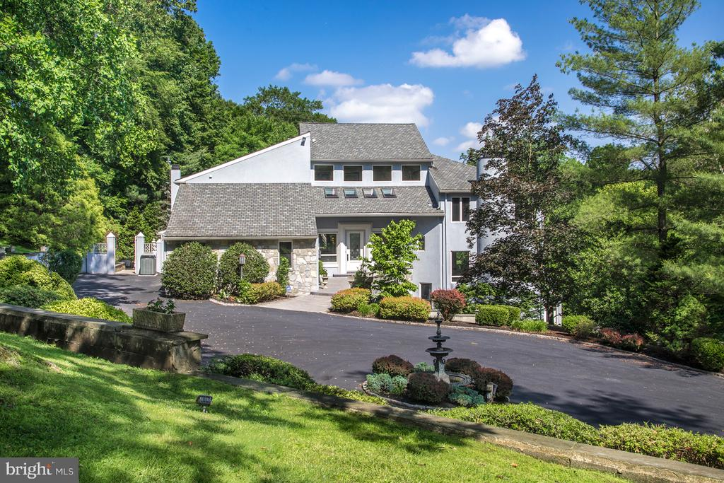 Home is currently tenant occupied. Settlement date will be end of lease term - 11/31/2021. Modern elegance is in full display in this exceptional 5 bedroom, 7.1 bath residence in prime Gladwyne, set amidst 3 private landscaped and wooded acres in the Main Line~s coveted Northside Mill Creek region. The experience begins with a long winding gated drive that proceeds through stunning grounds to a large circular drive, covered carport, and 5-car attached garage. A fabulous outdoor patio, 39~x18~ pool, regulation-size tennis court, and multi-tiered terraces round out the resort-like ambiance of this contemporary gem and ultimate family oasis. The front door opens to a sensational 2 1/2-story entry hall/gallery awaits, likening a modern art museum with soaring ceilings and expansive wall space for displaying artworks. Marble floors, a striking curved staircase, drop chandelier, and generous windows and skylights further dramatize this impressive space. The main level is designed for living and entertaining at its best. The gracious floorplan is highlighted by airy ceilings, wood and marble flooring, and generous glass inviting abundant natural light. Beautiful nature views are enjoyed all year round, from every vantage point. A spacious living room, dining room and family room set a tone of comfortable elegance for hosting and relaxation. The sleek, striking kitchen is fully equipped for the cook with granite counters and premium Miele appliances, with an open breakfast room, soaring ceilings and massive window wall bringing the outdoors in. On the second floor, an expansive master bedroom suite with a fireside sitting area, dressing room, and deluxe marble-clad spa bath provides a serene retreat. Three additional large bedrooms - one with a loft space, all with en-suite baths and ample closets - provide private quarters for family and visitors. An office/library features lovely built-ins and elevated views. The full, finished lower level boasts multiple entertainment areas, a bar, dance floor, family room, plus an office area and guest/au-pair suite with kitchenette. Beyond the gorgeous natural surroundings, you~ll enjoy living in close proximity to the village center of Gladwyne, shopping and dining, top local schools, all major transportation routes, and Center City.