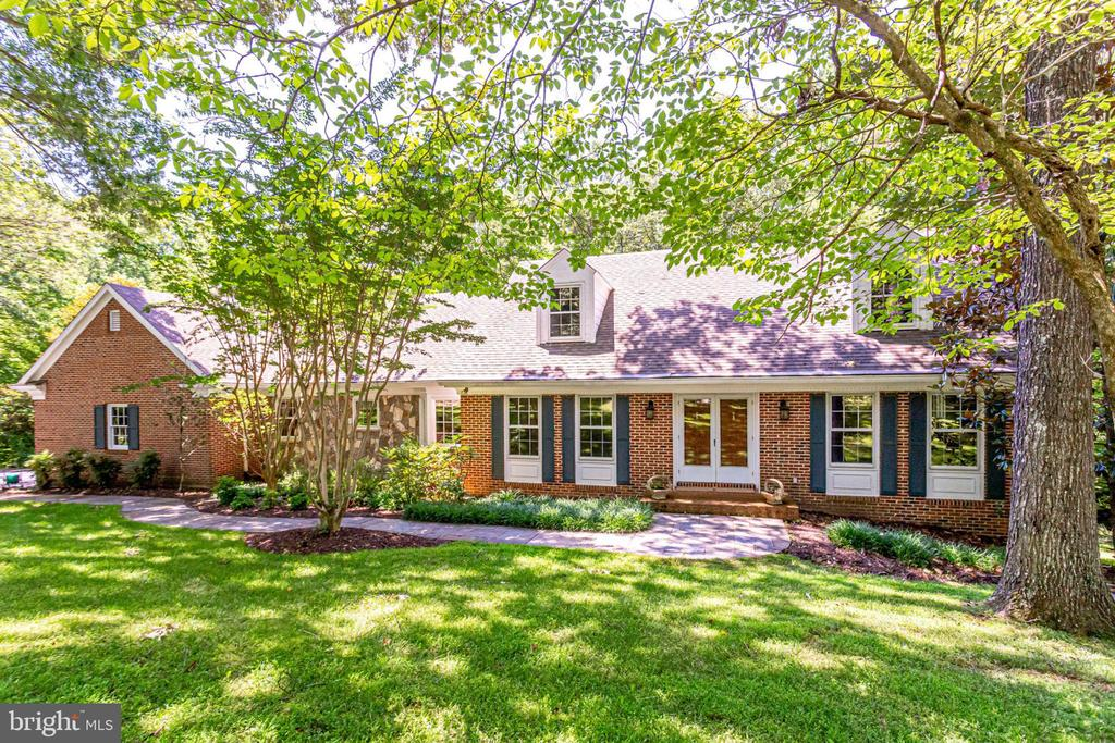 Amazing price reduction! Open Saturday July 20, 11-1. Welcome to the warmth and charm of 10415 Dominion Valley Drive~If you are looking for a retreat from Northern Virginia madness, you have found it on Dominion Valley Drive. This beautiful classic home on 5 acres has a stunning sunroom with vaulted ceiling and a view of the tennis court. The family room, living room and recreation room entice you to relax in front of the 3 cozy fireplaces, while the inviting country kitchen with granite counters, stainless steel appliances and a 6-burner gas stove creates a space for pleasant gathering. The washer and dryer are off the kitchen in their own quiet nook. Two bright and cheerful bedrooms with a full bath create a wonderful in-law suite on the main level and a second similar two-bedroom suite, perhaps for an au-pair, can be found on the lower level. The basement also includes a spacious recreation room with a wet bar or kitchenette which can easily become a full kitchen; a roomy office with built in desk and cabinets; as well as oodles of finished storage including a large cedar closet; a workroom for messy projects and a second full size washer with hook up for a dryer; there are outside entrances on the lower level from both the recreation room and office to the back of the house. The master bath has been renovated to include double sinks and a large shower stall. The two upper levels are all hardwood floors except for the sunroom which has beautiful slate flooring. The two-car garage is oversize with high ceilings, built-in shelving and space to park a boat. Every generation will find something to love in this exceptional property. Leave the hustle and bustle, but know everything you need is only a few short minutes down the road ~ The peaceful Shadowalk community is nestled between Lorton and Burke in the Fountainhead district of Fairfax Station. The neighborhood is extremely horse friendly with its own beautifully maintained trails. Only 5 minutes away, Fountainhea