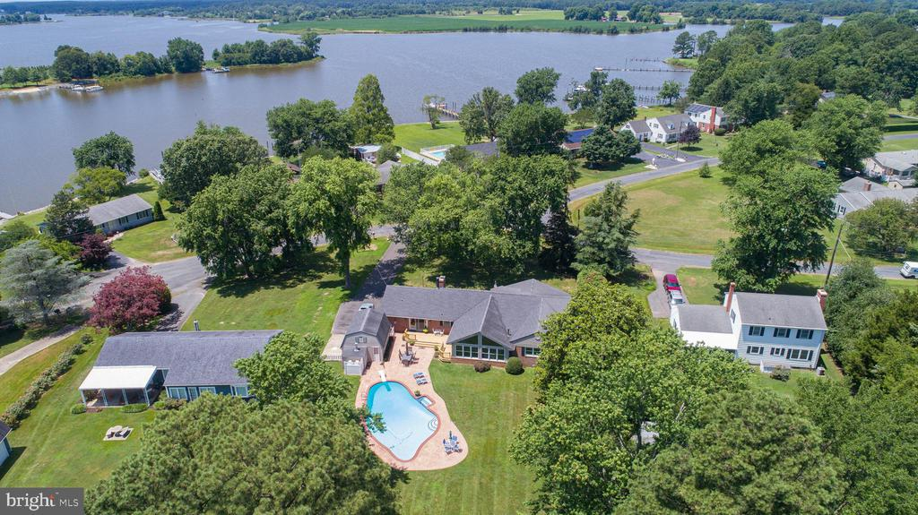 Deluxe 3,000+/- sf brick rancher with a private waterfront park-like setting. Attention to every detail - Silestone gourmet kitchen & 3 fireplaces. Waterfront fireplaced porch with forever views to enjoy. There is a brick patio around the pool but also a pier, boat lift, 2 jet ski ramps and rip-rap shoreline. Garage or workshop for hobbies.