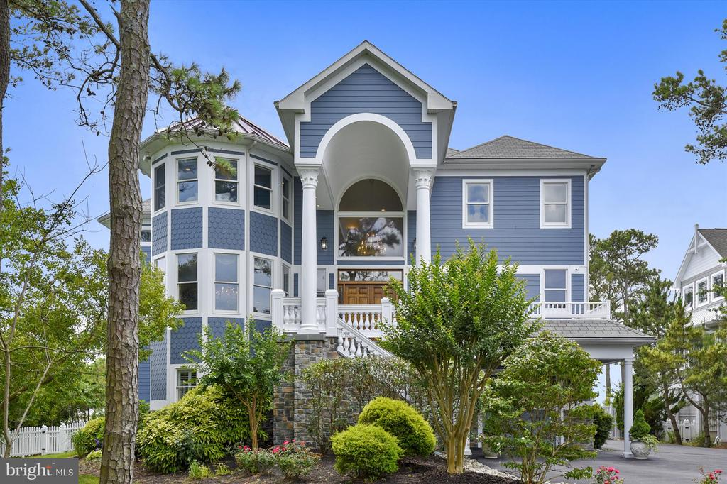 This luxury coastal oasis is 7,500+ sq. ft. with mesmerizing, panoramic views of the Sinepuxtent Bay, Assateague National Park and more! Residing within one of the area~s most prestigious neighborhoods, Ocean Reef, which is just a short drive from downtown Ocean City, this luxurious waterfront estate offers everything you could ever want in beach living with easy access to the Atlantic Ocean. Its close proximity to the Town of Berlin, which was named the Coolest Small Town in America, Assateague National and State Park and West Ocean City makes it a ~best of both worlds~ location near some of the area~s top-rated bars/restaurants, outlets, coffee houses, grocery and specialty stores, family fun and more. The exquisitely custom-designed floor plan includes three soaring levels with 6 bedrooms, (5 ensuite), as well as massive indoor and outdoor living spaces ideal for entertaining! Enter this magnificent home through the stately and colossal wood doors to the foyer and see regal columns and archways atop gorgeous rich Brazilian cherry wood floors! Follow the columns to the spacious great room and witness the exquisite craftsmanship of the circular wall of windows overlooking the bay, cathedral ceiling, built-ins and the striking floor-to-ceiling stone fireplace! Walk directly outside and enjoy the elegance and peacefulness of the large wrap-around deck. The massive, airy kitchen includes a jumbo center island with room to entertain a large group of guests, as well as several additional luxurious features: Jenn Air cook top with grill, double built-in convection ovens, Sub Zero large refrigerator, wine cooler, two trash compactors and two dishwashers and a walk-in butler~s pantry! Plus, there are 180 degrees of large windows to soak in those captivating coastal views! The first ensuite bedroom with an entrance to the deck is on the main floor. The formal dining room and theatre room lay adjacent to the foyer. On the 2nd level resides the master suite where the awe-inspiring views are even more enthralling - and yes, that is possible! The master includes a large balcony and 2 massive walk-in closets with built-ins and a full office space. The luxurious bathroom has an enormous shower and a jetted tub with sizable windows to peacefully gaze outside! There are 2 bedrooms, a front and back that have ensuite ~ baths and share a shower. The rear bedroom has a private balcony and a walk-in. The 4th bedroom on level 2 is ensuite and has its own atrium wall of windows! The ground level mudroom provides second entry point from both the 1 car and 2 car garages, as well as a side door. This level also houses an over-sized game room with wet bar and access to outside, a living room, additional bedroom, full bath, 2nd kitchen with 2nd W/D and gym. Exit to the backyard to find a stone, partially covered patio, hot tub and heated in-ground pool. There are 2 gas hook-ups for grills or firepit, an outdoor shower and a white picket fence. Go through the gate to take a long, tranquil walk on the pier to your 2 boat slips with 2 -10,000 lb. boat lifts and 1 waverunner lift!   BONUSES include: an Elevator, Plenty of Storage with hall closets, walk-ins, custom built-ins, cabinets and shelves. UPGRADES Galore: water views from most rooms, granite, Brazilian cherry on two levels, luxury vinyl on lower level, central vac, intercom system, surround sound, heated floors in bathrooms, electric shades in master & great room, in-ground sprinkler system, outdoor cameras & motion lights, security system, 2 staircases to access the 2nd level, 4 geo-thermal heatpumps (3 installed in 2018). SEE virtual tour for interactive floor plans, drone & 3D video. Schedule a time soon to come and see this exquisite dwelling in person! Life is Not a Dress Rehearsal - Own at The Beach!