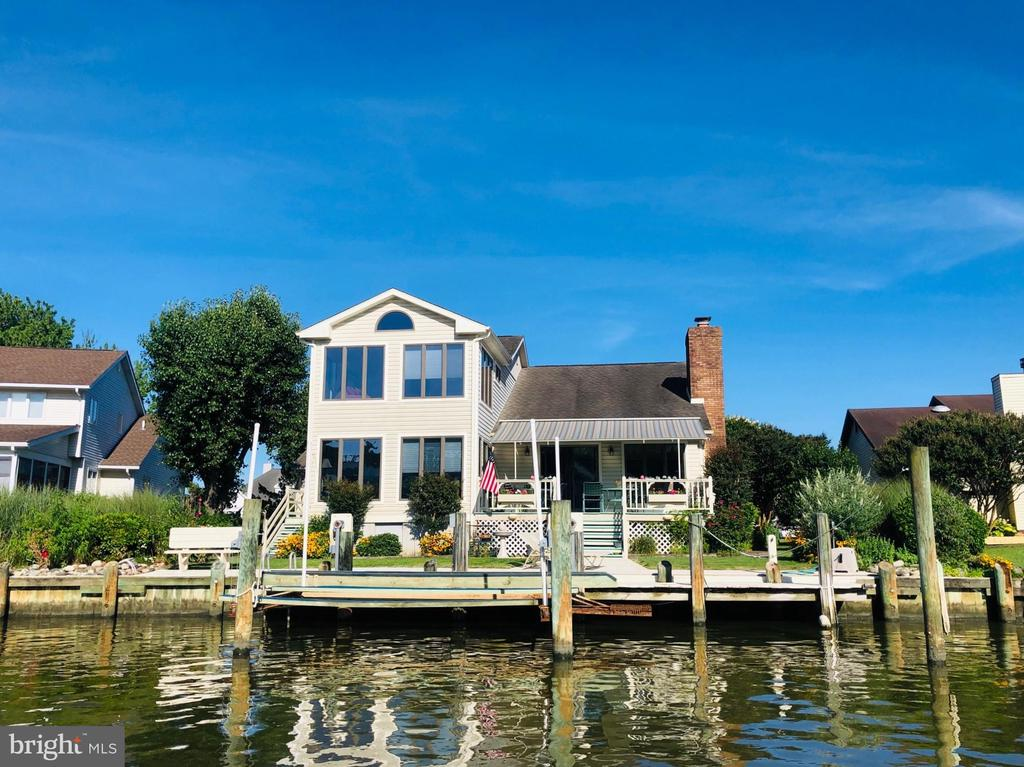 $10,000 SELLER CONTRIBUTION, AT SETTLEMENT FOR ACCEPTABLE CONTRACT, TO ASSIST BUYER WITH ANY DESIRABLE UPDATE COSTS! Located near the end of a Cul-De-Sac, just around the corner from the open waters of Manklin Creek and Isle of Wight Bay. Water enthusiasts will appreciate  the deep water dock with boat lift that also includes bunks for 2 jet skis. The rear garage door, near the outdoor shower, provides quick and easy access to your water toys. Renovated by the previous owner/builder and current owners addition of a waterfront Florida Room complete with half bath and another master suite offers views of Manklin Creek's natural wetlands. NEED A 4TH BEDROOM? The large 2nd floor Loft area with windows and closet area, could be just that. The Kitchen, Dining and Florida room combo is perfect for entertaining and the adjacent Living room with brick fireplace adds an additional area to relax and enjoy the water views. Both the Living room and Florida room provide access to your awning covered waterfront deck. In the over-sized and heated 2 car garage, you will find a large work space area with laundry tub and toilet. Whole house Surround Sound System, including garage and exterior speakers, convey. Don't overlook this one, possibilities are unlimited!!!