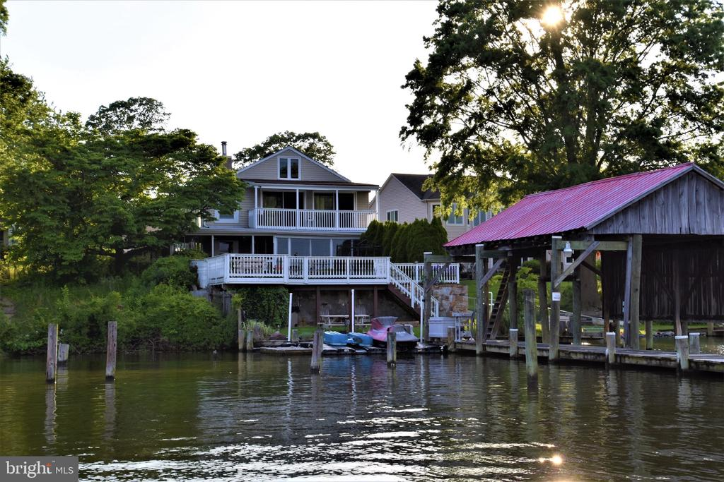 Flood insurance NOT required, Zone X.  Beautiful Waterfront Property with a Fantastic View, located on Norman Creek, which is one of the deepest creek in Essex right off Middle River. 70ft pier, Bulkhead, and Boat Ramp. 30ft x 14ft Boathouse. Detached 2 car garage with upstairs Apartment, Full Basement, Partially Finished with plenty of Storage, Fitness Room, and Walk Out. This Home has 5 Bedrooms, 4 1/2 Baths, New Replacement Windows, 2 Wood Stoves, and 1 Pellet Stove, 3 Heat Pumps, Ceiling Fans throughout, Master Bath Soaking Tub, Walk-In Closet, Sitting Room, and has its own Private Kitchen & Laundry. New Carpet throughout. Interior Freshly Painted. Security System for House and Garage with Cameras. Walk up to Large Attic that could be made into an extra Bedroom. In-Law Suite with Full Kitchen and Separate Entrance. This Home is Great for Entertaining,  5 Minutes from Crazy Tuna & River Watch