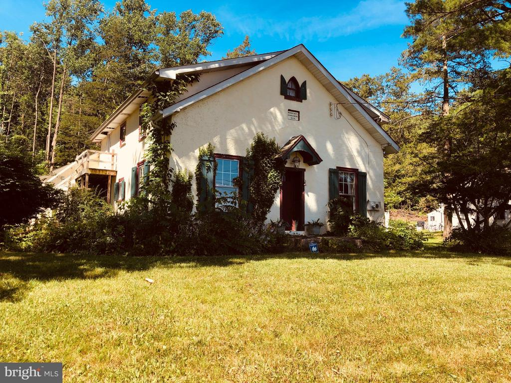 """INVESTOR OPPORTUNITY - The charming home was built in 1880 and now it can be yours. This property is full of history and charm. This is not your average farmhouse! Originally built as a Schoolhouse, it was converted to a Duplex (upstairs has a separate entrance from downstairs), then converted to a single home. Current owners began to convert it back to a Duplex, with the kitchen upstairs (former bedroom) partially complete.  Located in Harmonyville, it backs up to Pennsylvania State Game Land for ultimate privacy. It is very close to the historic community of St. Peter's Village.  The first floor has beautiful hardwood flooring, beamed ceilings and deep window sills throughout.  The living room will be your favorite place with its custom crafted fireplace focal point. The kitchen has character and functionality, with a convenient adjacent dining room with attractive stone walls. There is a Master Bedroom and full bathroom on the first floor, great for those seeking one floor living with income potential on the second floor.  The stairwell is in the rear of the house at the rear entrance, providing a convenient mudroom/foyer and access to the garage and basement. Up the stairs, find a beautiful great room with high ceilings and stone fireplace. The deck off the family room gives you a great space to entertain. Also, upstairs you will find two bedrooms, another large living area, a full bath, and a room that is currently a partially finished kitchen which could easily be converted to a bedroom. Adjacent to the family room is a space that can be used as a laundry room. The flexibility of this home is really appealing. There are many options for the second floor to suit your specific needs. This property is being sold """"as-is""""; the Sellers cannot make repairs.  May not qualify for traditional financing. Cash deals preferred.   Roof replaced in 2009. Property needs a new septic system and lots of work."""