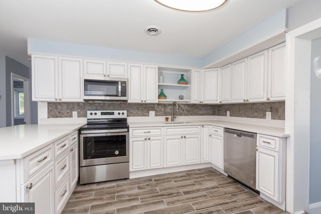 Newly renovated single family home in a desired neighborhood of Wilson Point. This home features open and inviting floor plan perfect for entertainment and family gatherings, brand new large eat-in kitchen with shaker style cabinets, quartz counter tops, stainless steel appliances, hardwood floors throughout the living and dining area. Master suite offers a large bedroom with a newly remodeled bathroom and spacious custom closets.  All bedrooms are on the entry level.  Main level mud room with a washer and dryer is conveniently located off the kitchen. Newly finished lower level offers a bonus room/family room with a walk out to the fenced-in back yard. Parking is made easy by a carport and a large detached garage on its on electric panel and a separate HVAC system. The architectural shingle roof and double-hung vinyl windows were updated in 2018.  Easy to show - waiting for the new owner. All things considered - this property is the best deal per square foot in the area!