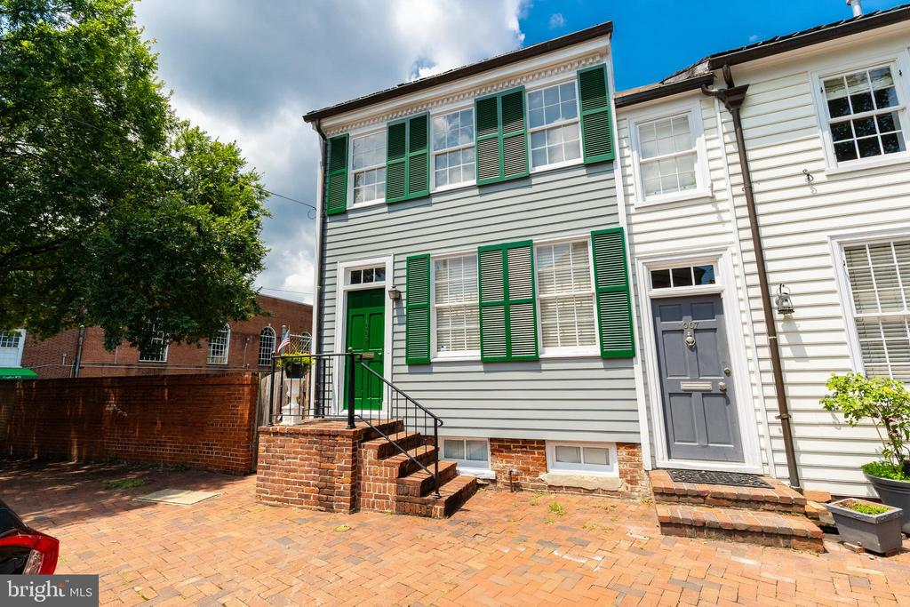 Open House Sunday, July 14th from 1-3 pm. Beautiful 1830's Federal Style End Unit Townhouse in Old Town Alexandria.  This stunning 2 Bedroom and 2.5 Bath home hosts a welcoming atmosphere on an extra large lot with plenty of expansion potential.  The just completed renovation includes stripping and refinishing the original hardwood floors, new kitchen with stainless steel appliances, updated bathrooms, and laundry installed. The property's traditional floor plan also features crown moldings, built in bookcases, exposed brick walls, multiple decks and patios, as well as a wood burning fireplace with a mantel saved from a 17th century church.
