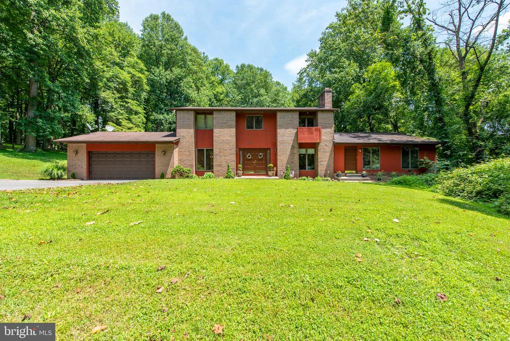 Tucked away on a beautiful wooded lot, just under 3 acres, this expansive Contemporary style home with private guest apartment exudes comfort and privacy!  Inside you~ll find a spacious, functional floor plan including a cozy family room adjacent to newly updated eat-in kitchen featuring stainless steel appliances, granite counters, breakfast bar, wet bar, and sunny breakfast nook with French doors to elevated deck overlooking sprawling back yard!  Entertain with style and ease in the formal dining room and sunken living room with wood burning fireplace flanked by built in bookcases.  Upper level hosts 4 comfy bedrooms, including a serene Owner~s suite featuring a spacious walk in closet, wood burning fireplace, attached full bath and French doors to private balcony!  Fully finished, walk out lower level, ideal for movie and game nights, boasts an expansive rec room with wood burning stove, game room, bonus room and a half bathroom.  Newly renovated, 2 level, attached guest apartment offers an open concept main level including living room and eat-in kitchen with 2 spacious bedrooms, a full bath and a private deck.  Lower level hosts 2 additional bonus rooms, a recreation/family room with access to backyard and separate laundry room.  This home boasts updated bathrooms, fresh paint in a neutral palette, new carpet and luxury vinyl plank flooring throughout!  Fantastic opportunity for multigenerational family living!