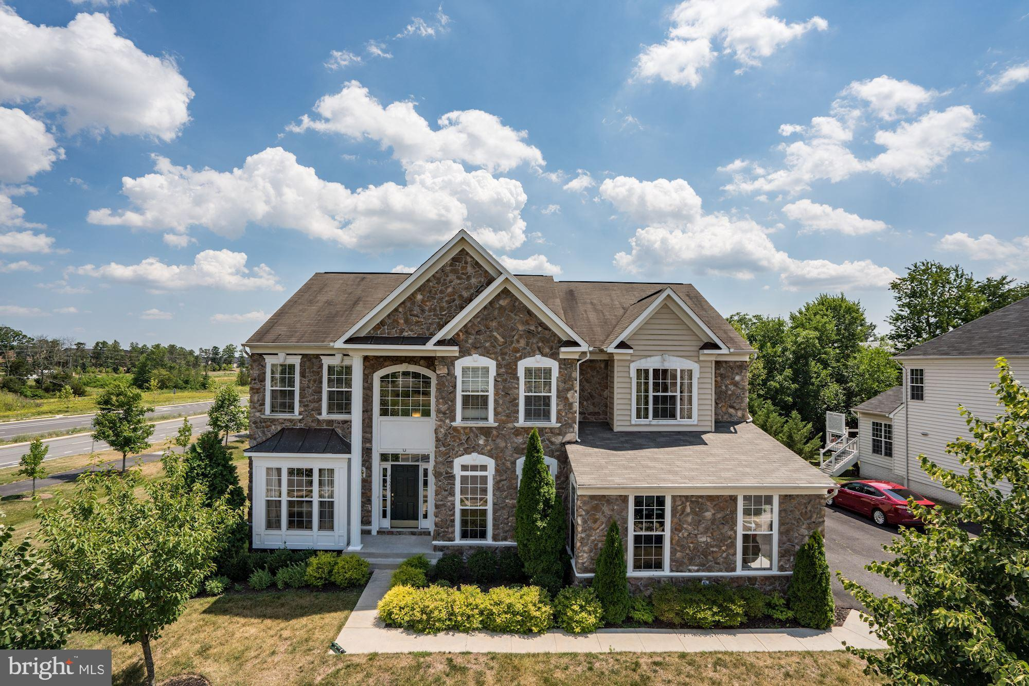 Open Sunday 7/14 from 1-4. Beautiful Stone Front home with 5 bedrooms, 4.5 baths, 2 car side load garage. Over 5330 SF total finished area on all levels; 3683 SF on above grade; 2-story Foyer; Elegant family room with coffered ceiling and fireplace; Office room on main level; upgraded hardwood floors; Built-in speakers on all levels; Gourmet kitchen with stainless steel appliances; Dual staircase; Sunroom off kitchen; Composite deck; Large Master suite with sitting room and 2 walk-in closets; Luxury master bath; Composite deck; Backs to trees; Basement has large recreation room, gym room, den, and storage area, Media room in the basement converted to kids play area; Walkable distance to Moorefield Station Elementary school; Close to Home Depot, Loudoun Station and Brambleton town center; About a mile drive to Toll Road and Future silver line metro station which is coming up in 2020.