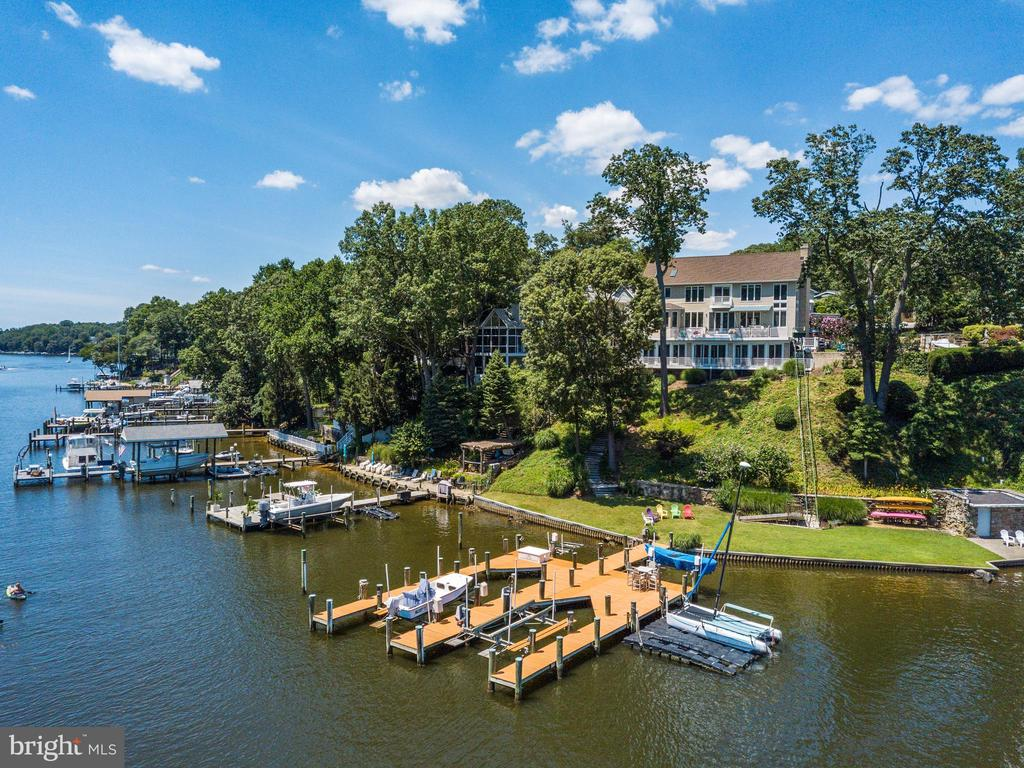Every once in a while you stumble upon a true gem; a masterpiece. This is one. Every inch of this nearly 5,500 square foot home has been meticulously maintained and updated with no detail overlooked and no expense spared. This spectacular waterfront home offers the quintessential waterfront life style people only dream of. With unobstructed, panoramic views of the coveted Severn River, you will look forward to coming home simply to relax on the deck or take a sunset cruise. Deep water, 140 feet of water frontage and a double, multi-slip pier that is rarely, if ever found, and offers three boat lifts and a double jet ski lift. Inside, you will immediately take notice of the grandeur and intricate detailing of this impressive home. It was built with the highest standards and finest materials to suit the most discriminating buyer. Gracious rooms, stone fireplace, hardwood flooring, a custom designed kitchen with quartz counter tops, stainless steel appliances, 9' ceilings and expansive water views from almost every room are only some of the exquisite features of this home. Feel your blood pressure go down the moment you enter the home and experience the commanding views through the wall of windows. Upstairs you will delight in the expansive owners' retreat with sitting room, vaulted ceilings and a luxury owners bath with a Jacuzzi tub and radiant flooring.  All bedrooms enjoy hardwood flooring, custom paint and each has its own en-suite. The finished lower level is the entertainer's dream! A 50 x 28 rec room, complete with a stacked stone bar and accent wall opens to a Florida room addition where you will relish the views 365 days a year! Take a moment to silence your mind as you look out the window to see the Great Blue Heron and Ospreys feed, nest and soar. Welcome home! We hope you will enjoy this home as much as the sellers' have.