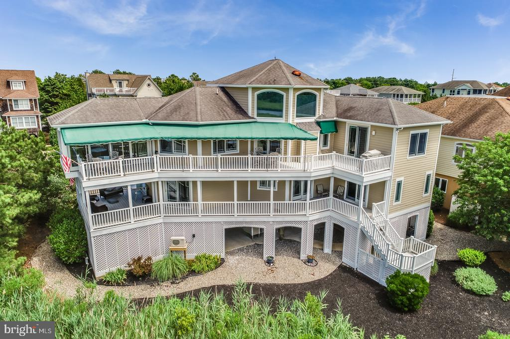 Waterfront N. Bethany bayside beach home with boat dock offers direct access to the Indian River Bay/Inlet & the Atlantic Ocean.  This one-of-a-kind spectacular 3400 sq. ft., 5 bedroom, 3.5 bath custom home is expertly-sited on a quiet cul-de-sac at the ~end of the road~ in the private gated community of Ocean Ridge West. Privileges of the Ocean Ridge community offer gated private beach access & community pool & tennis. Privacy & tranquility on multiple levels with elevator access throughout. Expansive multi-level outdoor living areas with panoramic water views & spectacular sunsets are accessible from all indoor living areas. The main floor offers an expansive great room that provides unparalleled water & protected land views for the privacy seekers. High-end finishes throughout include cathedral ceilings, ceramic tiled flooring, custom built-in cabinetry, wet bar with icemaker & oversized gas fireplace. The great room extends to the gourmet kitchen with custom cabinetry, granite counter tops, updated stainless steel appliances, an over-sized breakfast/gourmet-bar & dining area with a table that can accommodates 8-10 friends & family, in addition to the gourmet-bar seating for 5.  The second refrigerator in the pantry/laundry room offers easy entertaining preparation & execution.  The main dining area opens through to a newly renovated all season room overlooking the water & provides yet another access point to the wrap-around awning covered decks.Additional upgrades include parking for 10, 2 outdoor showers, 2 laundry rooms, 3 zone heating and cooling-2 of which are closed-loop Geothermal system, whole house central vacuum, security system & irrigation. Walk out your back door to your private dock & go for a boat ride, use the community pool for a convenient swim, launch your kayak or paddle board, or head to the private ocean beach!  Sold fully furnished and turn-key.