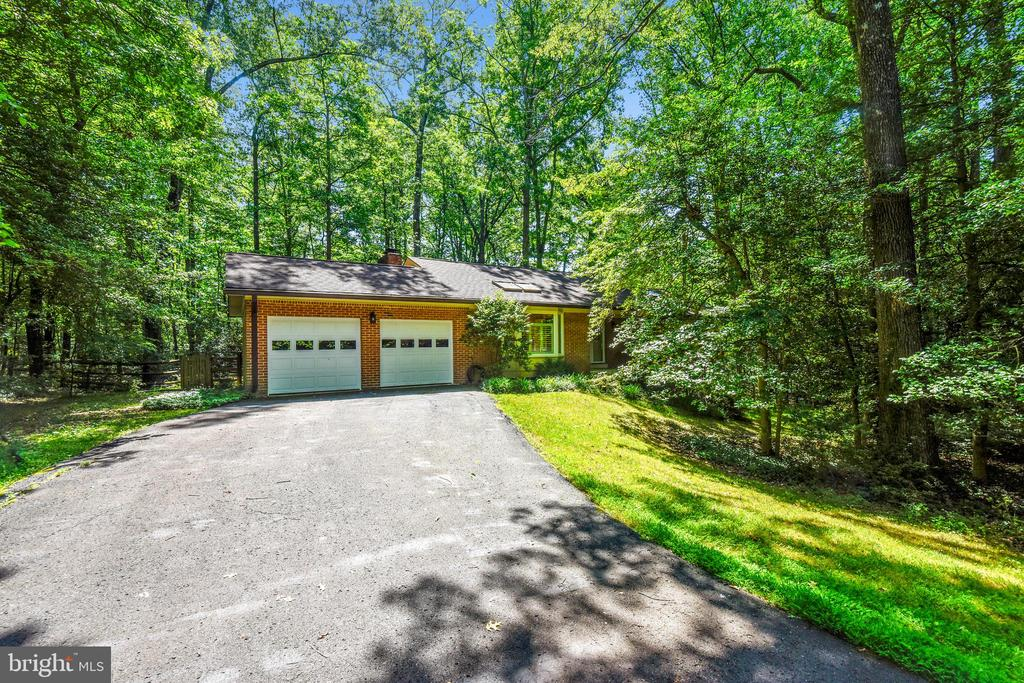 On a 1.24 acre private and secluded park-like tree/wooded corner lot, this welcoming home is a entertainer's delight in highly desired Reston, Fairfax County. Complete with remodeled gourmet kitchen leading into a open dining room/living room...brings you outdoors to a 22 x 22 private deck. A perfect setting for family and friends gatherings.   Back indoors on the Main Level, you will find the Owner's Suite and two guest bedrooms-with two extensively remodeled full bathrooms.  Owner's Suite boasts a remote operated skylight-for starry, moonlight nights.  Next is the 1352 sq ft fully finished downstairs complete with a full wall of brick and a romantic gas fireplace...giving you the opportunity to walk outdoors to your own private space.  Lastly, a HUGE InLaw/Au Pair Suite (4th-5th BR) awaits you with another extensively remodeled bathroom...complete privacy with pocket doors & separate exterior entrance.  Desirable two car garage with keypad & side entrance door*Special order window shutters, kitchen cabinetry rollouts, hardwood floors, freshly painted, extra storage in basement, additional attic flooring above garage, washer/dryer/extra refrigerator convey.
