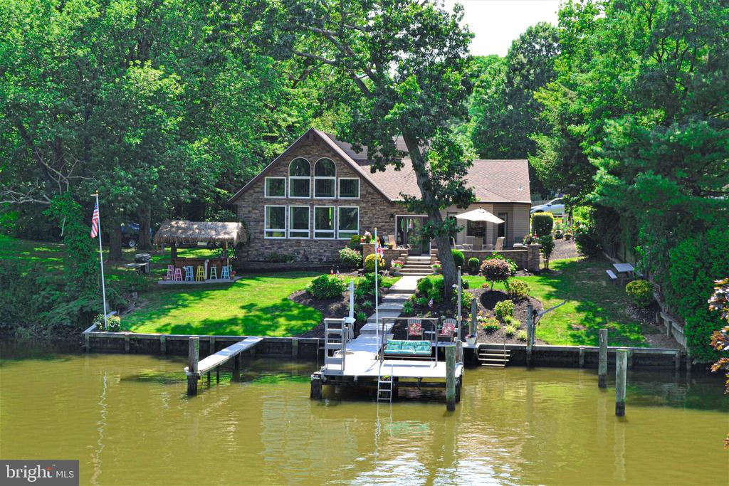 Gorgeous waterfront and endless updates!  Calling all WATER LOVING boat people! Ready to enjoy LIFE on the water with your own private dock & waterfront?  Are you looking for a perfectly maintained home with multiple deep water slips, stunning views with great swimming & fishing right out your back door?  You will feel like you are on vacation every day in this loved family house on the market for the first time EVER and just waiting for a happy new owner.  Wait until you see the fantastic custom Tiki Bar and maintenance free patio for entertaining family & friends.The UPDATE list is a mile long including a roof, HVAC, heat pump and new duct work installed within the last 5 years.  Set on a quiet cove with an 85 foot wide waterfront bulkhead, 3 boats slips (with a 5 foot mean low) & an electric jet ski hoist, you can enjoy the water every day.  Just 2.5 leisurely miles out to the Chesapeake Bay and plenty of waterfront restaurants and bars just minutes away.  You can skip the car for the summer and just travel around by boat!You will LOVE the open and bright interior with its gorgeous updated kitchen, STUNNING great room with cathedral ceilings and a WALL of windows overlooking the water.  Wake up every morning in your master suite to enjoy the calm beauty of Norman Creek to start your day. With 5 total bedrooms, 3 full baths and a main level laundry, this house has room for everyone.   Plenty of space to set up a home office or guest suite, the sky is the limit.  Great options for parking and storage as well, things you do not always consider until you realize you don't have it.  The spacious basement exists right out to the back yard for easy access to fishing poles and water gear and the 20x24 foot garage with electric was just built in 2016. Located in convenient Baltimore County, MD with great access to restaurants, shopping, recreation and culture.  Come see this house in person and get ready to make your BEST MOVE to life on the water!