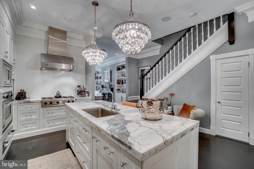 "This stunning T. F. Schneider designed Brownstone, located on one of Dupont Circle's most prestigious blocks, is truly a one-of-a-kind masterpiece. Built circa 1880 and thoughtfully renovated, it was redesigned for today's lifestyle by nationally renowned designer Lori Graham. This elegant home is suitable for even the most discerning buyer. Perfectly blended period and modern details can be found throughout the home including custom plaster ceiling moldings, a gas fireplace with inlaid marble surround and a beautiful chef's kitchen. Complete with custom cabinetry, honed statuary marble countertops, a ""Pro 48"" Sub-Zero refrigerator, a Viking range and a hidden paneled door that opens to a large pantry room, no detail has been spared. The dining room, ideal for hosting large-scale dinner parties, features classic pocket doors, a gas fireplace and custom drapes. Meticulous details continue on the second level where a soundproofed laundry area with oversized washer and dryer is situated between two well-appointed suites. Spanning the entire third level is another, extraordinary suite, features a sitting room, an additional kitchen with top-of-the-line appliances, as well as a massive bathroom with ebonized oak custom tumbled Nero-Marquina marble tile floor, separate vanities, soaking tub and shower. The sitting room of this jaw-dropping suite has 22' vaulted ceilings, floor-to-ceiling bookshelves with library ladder and four large custom skylights. Take the elevator up to the stunning two-level 600+ square foot deck that includes multiple seating areas and storage. The large lower one-bedroom apartment can be used as a separate income unit or additional living/guest space. Situated on a deep lot, the property allows for a back deck off the dining room and a fenced back patio for more outdoor entertaining space. Additional features include a Sonos systems with cameras, speakers, and wireless thermostats. Two car private parking rounds out this remarkable property."