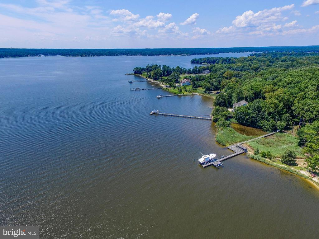 "BOATER'S PARADISE !!  Large waterfront home on over 2 acres on the Magothy River.  FOURTEEN FOOT water depth at end of pier. Commercial grade pier with two slips and lifts - One will hold 60 ft at 80,000 lb / the other 40 ft at 60,000 lbs.  Surrounded by agricultural and preserved properties.  VERY PRIVATE.  With over 5000 sq ft on three levels - this home has a fantastic wide open floorplan designed to take advantage of the spectacular water views from nearly every room. Tremendously solid construction.  This is the perfect waterfront for anyone who enjoys boating or simply enjoying the relaxed waterfront lifestyle. Covered screened Porch/Meditation/Yoga Room off master bedroom .. enormous Master Bath with separate shower and soaking tub. Possible 5th bedroom.  Numerous decks and plentiful built-ins throughout.  Move in ready - or add your own personal touches. Two car garage parking, storage shed, ""dog house"", and Screened gazebo and sun deck located on the pier.  This is what waterfront living is supposed to look like."
