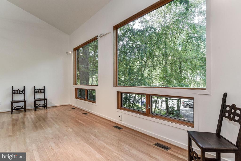 Priced to sell now! TWO SIGNIFICANT STRUCTURES ARE INCLUDED IN THIS OFFERING AND PRESENT A UNIQUE OPPORTUNITY FOR A RENTAL  UNIT, ART STUDIO AND WORK SPACE, A HOME BUSINESS, OR PROFESSIONAL OFFICE SPACE.  The four bedroom home, surrounded by trees,  has views in every direction, floor to ceiling windows and soaring ceilings. The property is located at the end of a cul de sac and adjoins park land. A greenhouse adjoins the family room and connects to a deck and terrace. ACROSS THE  COURTYARD IS A THREE LEVEL STUDIO BUILDING DESIGNED BY TOM MANION, ARCHITECT, WITH WOOD FLOORS. THERE ARE 12 FOOT CEILINGS IN THE MAIN GALLERY AND  WORK STUDIO.  THERE IS A KITCHENETTE, A FULL BATH, AND LOFT SPACE ON THE THIRD LEVEL. THE STUDIO BUILDING HAS SEPARATE HEAT AND CENTRAL AIR.  Both buildings together encompass more than 5500 square feet of space.
