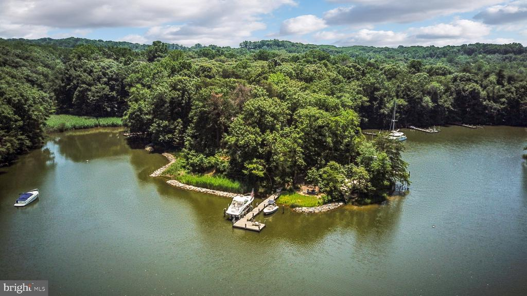 This stately waterfront home hits the market for the first time in fifteen years. Situated on a one acre+ point lot in sought-after Ulmstead Cove, a wonderful community of thirty-eight homes on the Magothy River just north of Annapolis, this resort-style home makes this a truly one-of-a-kind property.The living shoreline stretches nearly three hundred fifty feet of waterfront, wrapping the entire point of land. This backyard is an entertainers paradise. Enjoy your private sandy beach, kayak rack, waterside firepit, custom Pebbletec pool, pond with waterfall and fully stocked outdoor kitchen. A private pier with multiple slips, equipped with a new twenty thousand pound remote control boat lift, fresh water and electric, and swim ladder are perfect for water lovers. There are magnificent sunsets from the pier, patio, and pool deck.A long private drive takes you to an impeccably maintained brick-front Colonial, wrapped in new hardiplank siding, architectural shingles and low-e windows. Tastefully renovated over the years with a mix of traditional and modern elements that everyone will love. Fully renovated gourmet kitchen equipped with gas cooking, granite counters, stainless steel appliances, custom cabinetry, and custom kitchen island with imported African wood countertop.Multiple living spaces on the main level afford a hangout for everyone in the family. There are four bedrooms upstairs and one in the basement, along with five upgraded bathrooms with granite and marble finishes throughout.Fully finished basement with a great guest space, includes multiple living spaces, a custom bar and mini-kitchen; providing access to casual waterfront dining. Basement level workshop w/storage and walkout to pool deck.The community offers an adjacent sandy beach with a picnic area for neighborhood events, kayak racks with a launch, a fishing pier with fresh water, and a sports court with basketball, tennis and pickle ball. The neighborhood is in the heart of the award winning Broadneck school district and just minutes from Route 50 and Interstate 97, with easy access to Annapolis (by car or boat), Washington DC, Baltimore, the Eastern Shore and BWI Airport.