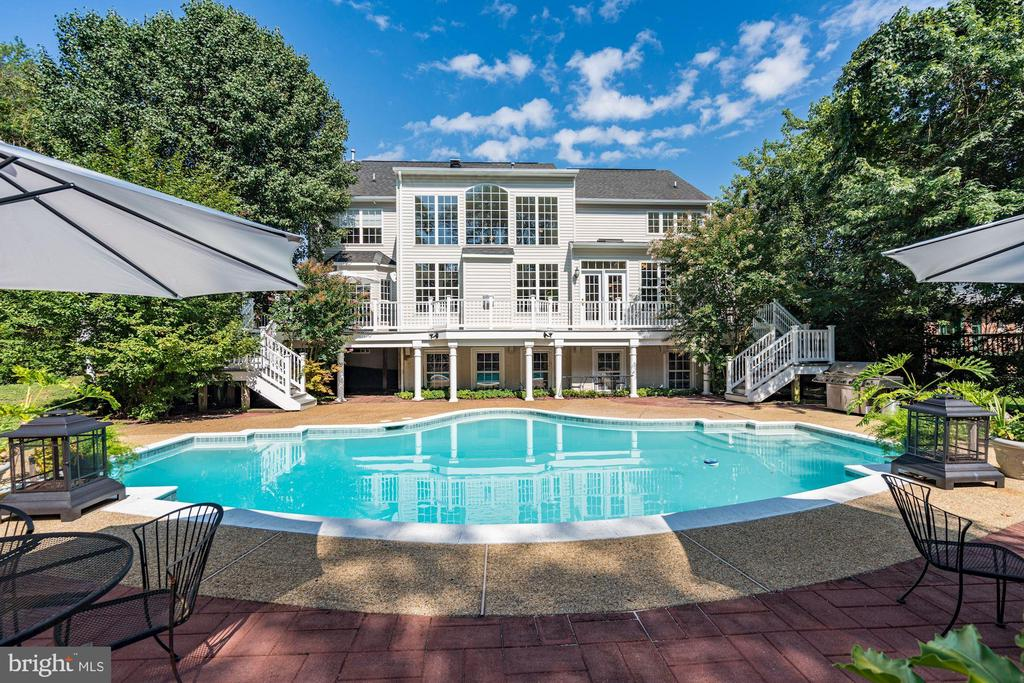 Rare, very Quiet and Private wooded compound in the city, this completed newly constructed custom built home is a one-of-a kind diamond in the neighborhood! Step into a hidden colonial enclave surrounded by huge perimeter trees and an in-ground pool making it one of the most private settings in Northern Virginia. This grand luxury home, situated in McLean, is located within a couple of miles of the West Falls Church Subway and Metro system, and just within a few miles of both National and Dulles Airports. This home has an open floor plan filled with upgrades, from hardwood floors throughout downstairs and upstairs, granite countertops, and GE Monogram stainless steel appliances featuring a self-cleaning oven, a six-burner stove, with a built-in microwave and range. The open breakfast area is just waiting for you to fire up the burners for your first meal pulling side items from the butler~s pantry. There's also a great room that models as a home office or library with picturesque windows looking out over the backyard.You~ll discover added skylights just so you can hear the rain tap on the glass. What feels like an all glasshouse is filled with warmth and hospitality. Another special amenity is the double pane windows traveling from floor to cathedral ceilings providing a ~walk in the clouds~ experience every which way you turn. You~ll notice the crown molding complete with a chandelier that easily comes down from the ceiling for cleaning along with the ability to switch on the marble gas fireplace to calm cold evenings. This warm home has been well lived in and cared for, and it~s now ready to open itself to a new family. Picture yourself entertaining scores of guests near the island kitchen then walking out to a wrap-around porch overseeing the in-ground pool. The enchanted gardens and special decks will have your guests feeling right at home before they jump into the pool. Directly off the kitchen is a 3-level bump-out professional studio/In-law suite/au pair suit