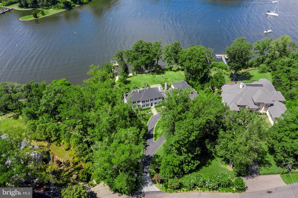 "The prestigious neighborhood of Wardour is home to Bridgewater, one of Annapolis' finest waterfront estates.  This lush enclave where the shimmering waters of Weems Creek branch off the Severn River is a stunning setting for this 5-bedroom executive estate that is perched high on a bluff over the creek. You will enjoy 180-degree water views and 250 feet of shoreline with a deep-water dock that can accommodate sailboats and cruisers.This stately Colonial-revival home, continuously kept in pristine condition since 1937, is at once a world away and within easy access to major routes toward Washington, Baltimore and their airports. Rowe Boulevard, Annapolis~ main artery, is but a three-minute drive, yet it does nothing to interrupt the peace and privacy of Wardour's park-like peninsula. Even better, this quiet retreat runs on the easy pace of the Eastern Shore without the hassle of crossing the Bay Bridge, while the shops and restaurants of West Annapolis are an easy stroll down leafy streets. You know you've arrived once you turn onto Bridgewater's graceful, winding drive, lined with flowering hydrangea and ornamental grasses overflowing from the gardens. The estate~s crisp white brick and black shutters quickly come into view~just as the verdant landscaping blocks everything else out. That's an important quality for families seeking total privacy for their weekend or full-time escape. The home's capacity to sleep up to 20 people makes it perfect for holiday celebrations with multiple generations; weekend house parties; even corporate retreats. The home, originally commissioned for a decorated Navy rear admiral, was always meant for entertaining on a large scale. The gracious proportions of its public rooms; its elliptical Great Lawn perched like a ship's prow over the water; a screened porch and its large outdoor dining area offer an easy flow for dozens or even hundreds of guests. Modern architects working in the traditional vernacular often design new revival-style homes to look old, as if they had been added on to over time. Bridgewater is the real deal: a small wing to the side houses what is now the heart of the home~a spacious family room and kitchen~while another addition on the other side is indistinguishable from the original central structure, though it adds crucial modern amenities such as an expanded master suite and dressing room on the top floor, a home office below, and a lower-level guest suite.  Bridgewater enjoys 250 feet of waterfront access that's beautifully defined with pea gravel and white oyster shells. This ""Pebble Beach"" is wide enough for lounge chairs, and also has room to store kayaks or laser boats for long, lazy days of running up and down the creek. The L-shaped deep-water pier off the bulkhead offer an 11-foot depth to accommodate a sailboat and powerboat, and there's a lift for a jet ski. From here, it's just a short sail out to the Severn River, where you can pass the Naval Academy on your way out to a day of cruising on the Chesapeake Bay, or to downtown Annapolis to grab dinner. Whether you desire to make Bridgewatera gathering place for a large family on weekends or an executive residence to host small dinner parties for clients, plan larger cocktail parties for employees and prospects or to entertain friends from around the world, this house has an exceptional flow that easily accommodates large and small gatherings alike."