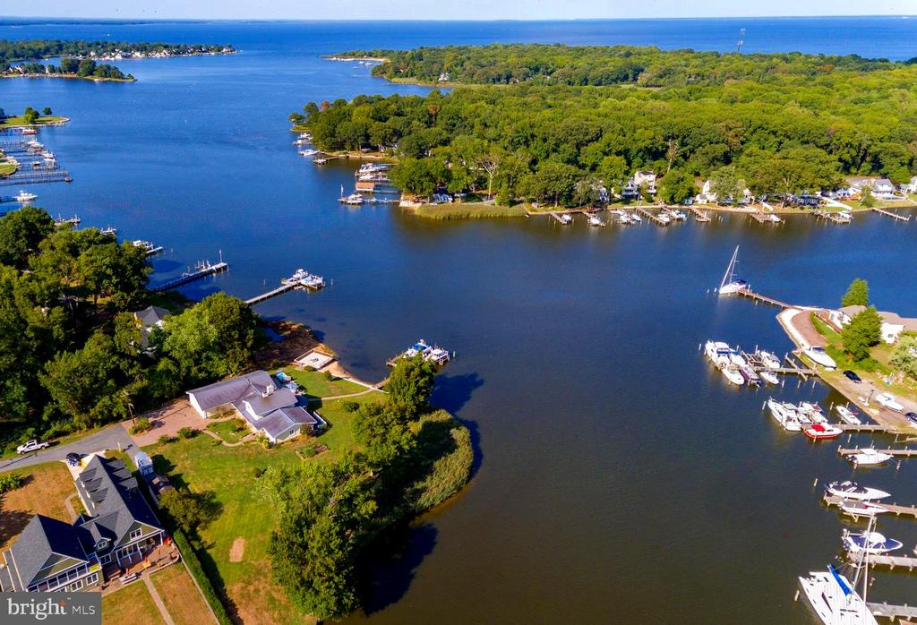 Sought after and rare point of land home on Bodkin Creek. Deep water and privacy on over 350' of Waterfront footage. This well appointed home has luxury finishes and astounding views clear to the Chesapeake Bay. Dock w dual lifts, over-sized garage, beautiful hardscapes, Swim Spa, hardwoods and recent addition of a true Chef's Kitchen with Butler's Pantry, custom cabinetry, Calcutta Gold marble & walnut counters as well as Built in appliances and cathedral ceilings and beams to start. Enjoy multiple Entertaining spaces indoors and out. You will not be disappointed the moment you set foot on this compelling piece of paradise.