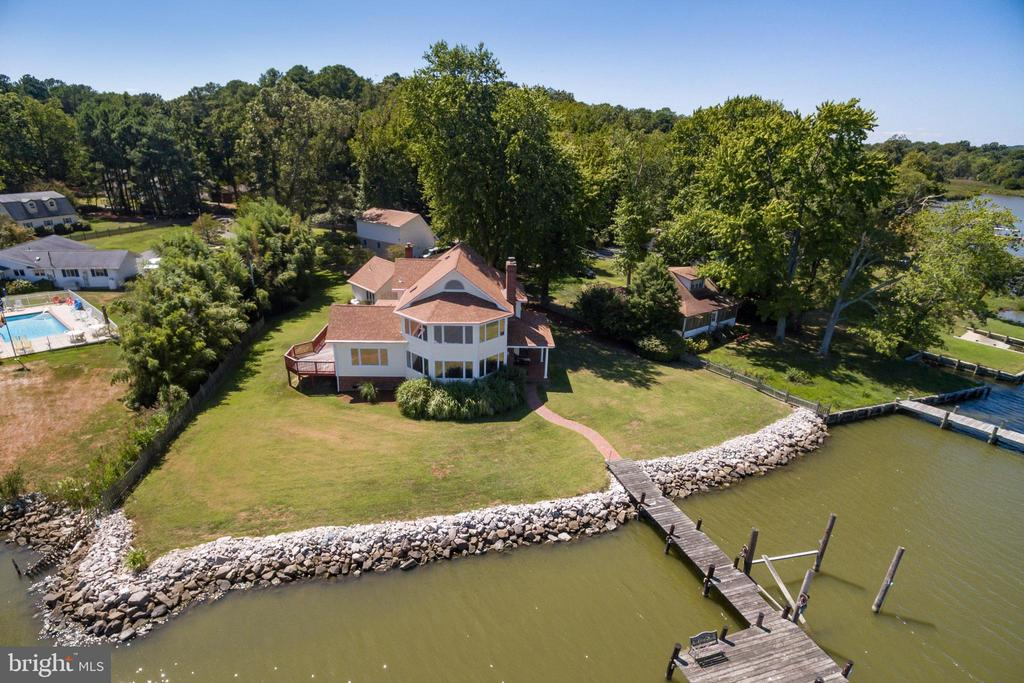 Have you been searching for the PERFECT WATERFRONT home? Would it have 180 degree views from the great room, dining room, kitchen and master suite?  Would it be on a protected creek but right at the mouth of the Chesapeake Bay? Of course you need a private pier.  But you have lots of precious cars that you want a 3 car garage for.  Then you entertain, you need parking for your guest too.  Since you might have scaled down, where will all your storage go?  The garage has full size  walk up steps to a floored space for storage.  Wouldn't it just be perfect to run your business from your home too?  How about a private separate office (with a water view) and a half bath?  But you need storage for your files and business equipment too. So this building has a separate staircase with a floored space above it which is just perfect for that too! So you don't want to settle for a small master bedroom with no closets either. How about two walk in closets, vaulted ceilings, panoramic views of the Chesapeake Bay and wildlife?  A hot tub inside the house might be nice too, let's put it on the second floor master suite.  So if all of this in not enough for you, it's also priced under a million and has a 6 year old roof.  Don't walk, you better run for everything this house has to offer.