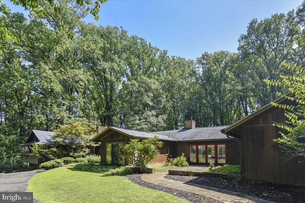 This magnificent one-of a kind custom designed and built cedar home is a tribute to the architectural style of Frank Lloyd Wright and the thematic ~of the hill~ not ~on the hill~ leitmotif.  It is sited on almost three acres and exudes tranquility as well as beauty and privacy.  Providing additional appeal, the 95-acre Meadowlark Botanical Garden is located across from the property.  The expansive space flows from room to room revealing both the versatility and utilitarian aspects of the home.  The exceptional quality of the structural elements is evident in the 2 x 6 on 2 x 4 center wood and stone construction, 5 HVAC systems, 1 gas, 3 wood and 1 wooden Belgian Eifel stove fireplace, vaulted ceilings, recessed lighting, walls of glass doors and fixed glass, 3~ wide doors, 12 sets of French doors as well as many built-in elements throughout the home.  There are steel I beams in lower level rooms which allow space to be transformed into bays for up to six cars.  One wing of this amazing home is comprised of an indoor swimming pool with a number of adjacent rooms, including versatile two-story space currently used as a home office.  The circular iron staircase in the bedroom area was originally a standard staircase and was converted to create more space in that area.  Whole house generator assures that the HVAC, kitchen appliances and much of the house continues operating normally when the power goes out.