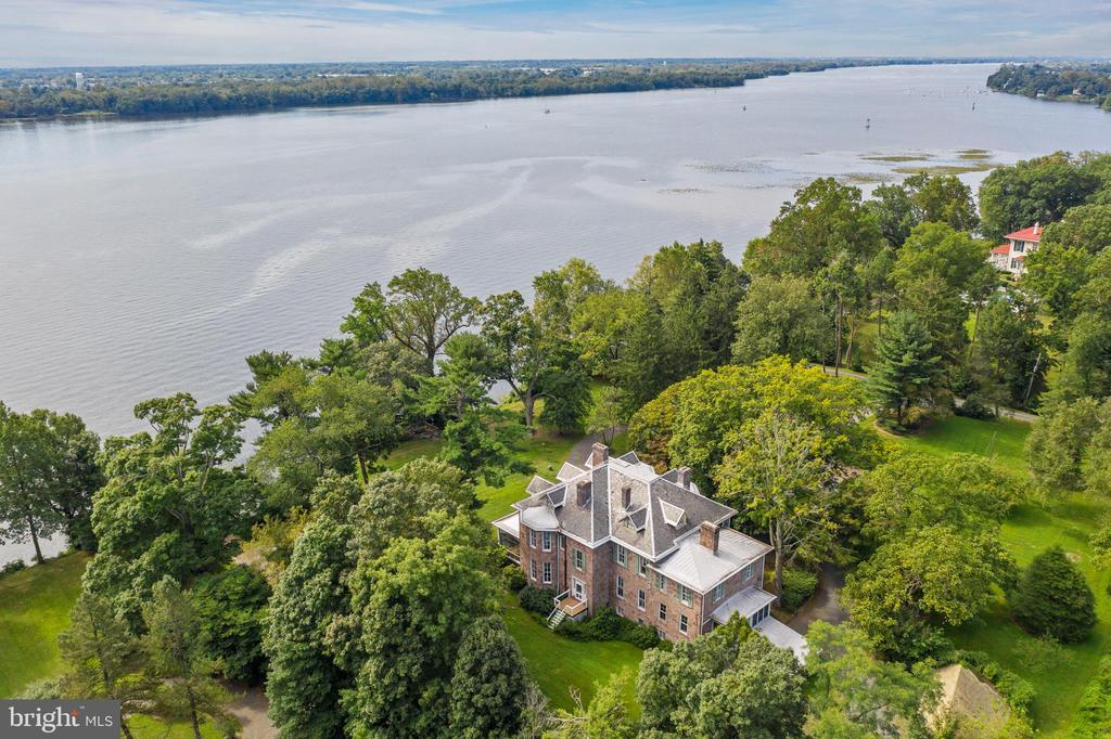 Feel worlds away perched atop the bank of the Delaware River, this almost 8-acre estate is truly magnificent offering old world charm and privacy in a convenient setting. Less than 25 minutes to downtown Philadelphia, the serene setting is sure to help you decompress after a long day. The main house is exemplary of Victorian opulence and style, grand and accentuated by a gorgeous and expansive front porch. With impressive ceiling height and truly magnificent water views, the porch sets the tone for the many thoughtful details and appointments of an 1857 stone manor home. The reception Foyer is inviting and showcases the formal Living Room with 10~ pocket doors, rich hardwood floors and walls of windows highlighting the spectacular views. The Music Room offers equally impressive river views and opens to the gorgeous Dining Room, allowing for wonderful entertaining overflow. Offering amazing space, this 6-bedroom, 4.5 Bath home has wonderful storage and flexible space to be utilized in numerous ways. Handcrafted moldings, millwork, over 12~ ceiling heights, cozy Study with mercer tile surround, fabulous Butlers Pantry and phenomenal fireplaces, outdoor space and outbuildings make this a truly unique gem. Separate guest quarters for in-laws or au pair, fishing/boating for the outdoor enthusiast. Outbuildings include: Carriage House, Cottage, River House and Barn suitable for multiple generations. Located in Zone A-an area determined to be outside the 100-500-year floodplain. Timeless property that is ready to be rediscovered!
