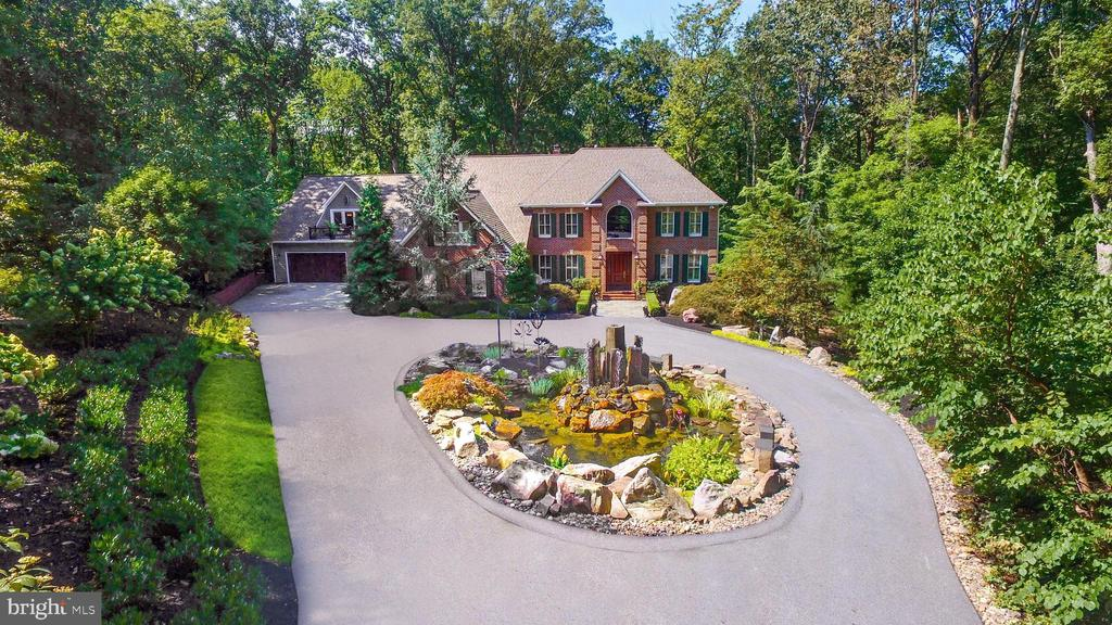 This custom-built, gracious home is an Entertainers Dream! Sought after cul-de-sac location to a gated driveway to 3.47 wooded ~privacy plus~ acres! Enjoy complete multiple outdoor living spaces including a four-season deck!  Greet your guests at the circular drive entrance, graced with multiple fire fountains and an artistic water installation!  Just Breathtaking!First impressions are lasting, and so is the grand  two story foyer and family room w/overlook!  A floor-to-ceiling masonry, two-sided fireplace graces the Main House family room and kitchen! AND, of course, two kitchens are a must!  The recent, professional, stainless steel service kitchen offers high-end ~master chef~ appliances, fixtures and professionally designed pantries!Upstairs, an amazing Owners retreat offers an enormous bedroom with w/cathedral ceiling, new hardwood floor, sitting area and a room-sized, walk-in closet. En suite bath includes a seamless glass shower w/stained glass tiles, a bubble tub, and radiant heated floors and heated towel racks!A work-out, spa-inspired, lower level offers a gym-like retreat, sauna, full bath and stunning laundry!  A beautiful wet bar is so convenient in the family/game room area!  This level also includes a room-sized walk-in closet!The Rear Deck which runs the length of the Main Home, has covered seating, a Basalt Built in Bar Area & multiple areas for seating and relaxing overlooking the spectacularly coiffed rear property space.  A Fire Pit centers the entertainment & gathering space down below the deck area, surrounded by beautiful rocks & plantings. The Guest House has its~ own heating, cooling and hot water heater, separate from the Main House.  First Level Laundry w/upgraded Front Loading Washer and Dryer & Granite Utility Sink is so convenient.  Upstairs is the Master Bedroom w/Plantation Shutters, walk-in closet and cozy office.  The Living Area is just perfect with beautiful rear property views.  The Updated Kitchen, Dining Area and Deck overlook the Front Gardens and the scenic approach to the home.Over a Half Million Dollars in recent upgrades to the property~s systems, roof, siding, soffits, doors, flooring, lighting, landscaping, and much more, elevate & enhance your living experience.This home is truly your Sanctuary!