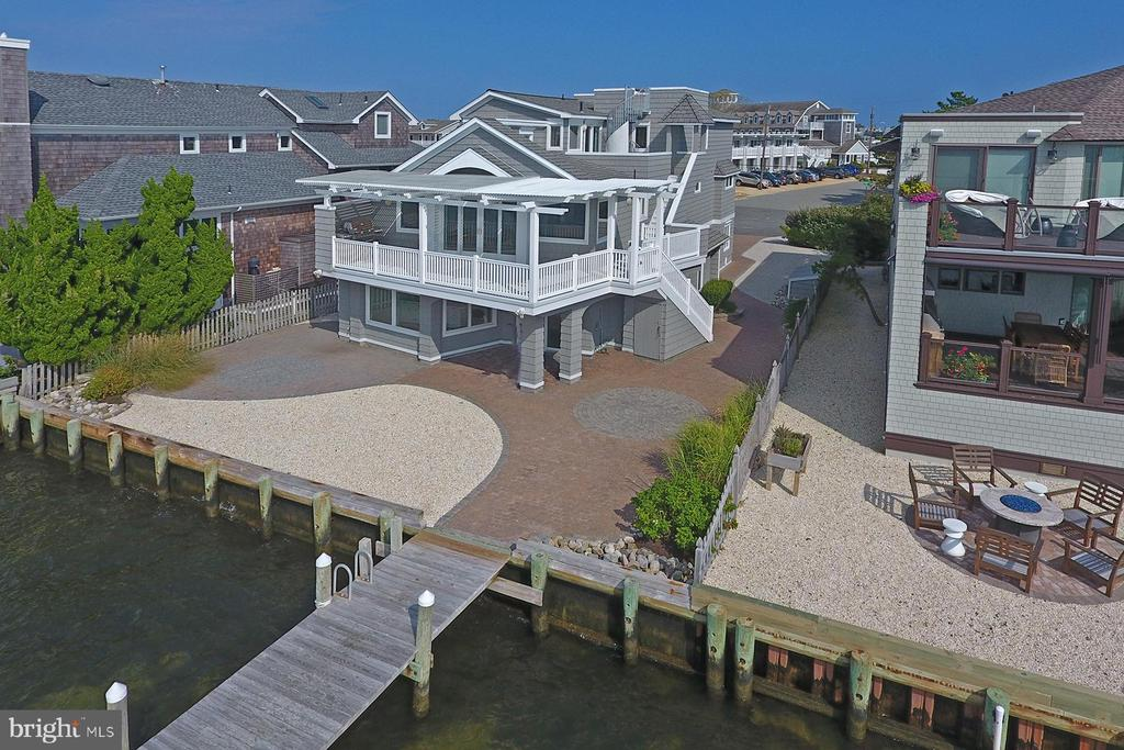 OUTSTANDING VALUE!  Coastal shingle style bayfront home in Harvey Cedars on an over sized 6,500 sq' site with 58' of bay frontage, huge dock, along with expansive bay and sunset views!  Features include 4 bedrooms (3 en suite); 5 full baths; bayfront great room with cathedral ceiling opening onto the large bayfront deck with power louvered pergola; large family room with surround sound and bay views (could easily be subdivided for a fifth bedroom and a family room); private upper level master suite with wet bar, whirlpool, spa shower, double vanity, enormous walk in closet, vaulted ceiling, and great bay views; dry/wet sauna; multi-purpose room that can be a gym, office or another living area; hardwood floors; central a/c; gas hot water baseboard heat; laundry room; 2 car garage; tons of storage; beautiful irrigated landscaping; brick drive, walks, and patio; riparian grant; and a 125' dock with seating that can accommodate the largest of fleets!