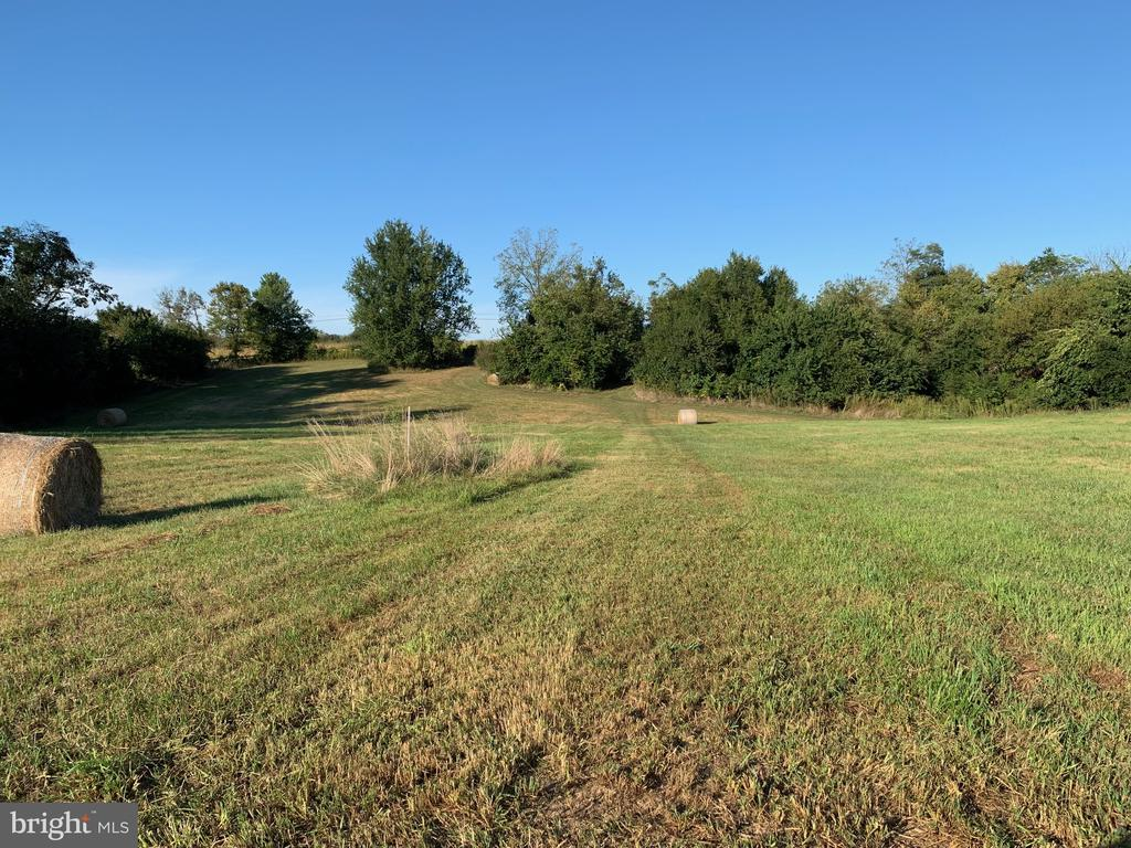 Location, Location, Location!  7,189 acre building lot adjacent to McMurran Farm Subdivision surrounded by scenic farm land and large estates.  Unbelievable sunsets, sunrises, and scenic vistas viewed from this location...absolutely priceless.  Lot was approved in August of 2018 for Class II septic system.  Buyer can re-perc another area if preferred.  Currently used for hay production.  Lot allows several different building options/house locations/etc.  Light restrictions.  2,000 sq. feet minimum square footage and must use natural exterior components.  A must see property!  Owner is a licensed WV Agent/Broker.