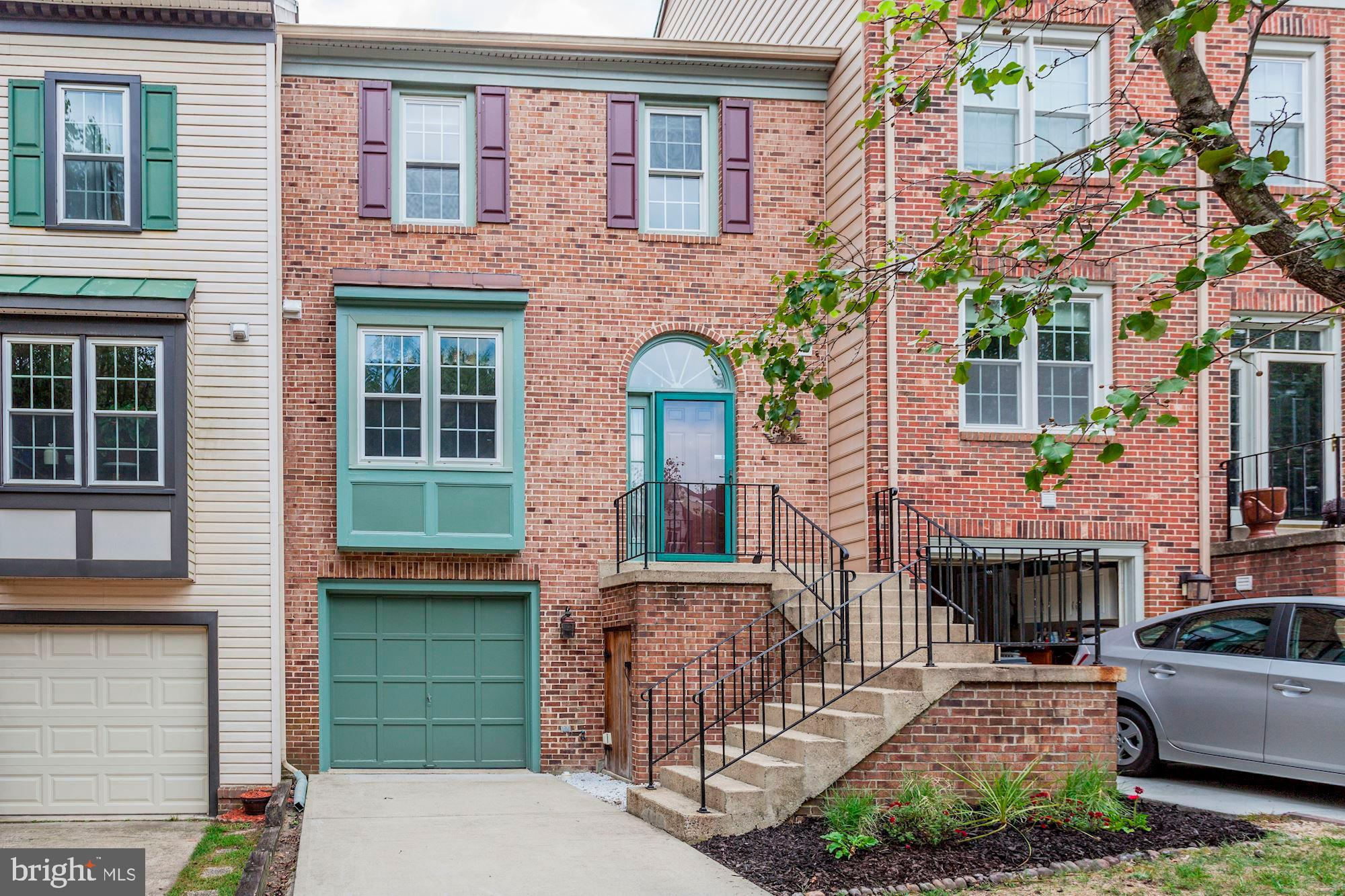 Brick three level garage townhome backing to woods.  You cant beat this location just off the parkway near metro stop, metro rail , trails and parks.  One car garage with two more spaces in the extra wide driveway.  Loads of natural light & vaulted ceilings in this open floorplan home. Remodeled kitchen with granite,undercounter lighting, undermount sink and tile floor.  Step down living room with marble surround fireplace & access to deck. Dining room with new brush nickle chandelier and room for a hutch. Master suite with cathedral ceilings and his and her closet with organizers .  Luxury master bath with separate tub and shower, tile surround and his and her sinks. Full walk out basement with double windows and SGD, brick fireplace, separate finished laundry room & half bath.  The front yard is mowed by the association.  The back yard is so little maintenance with a concrete covered patio and brick patio facing the trees. Dont miss the great storage area under the front stoop its larger than it looks.