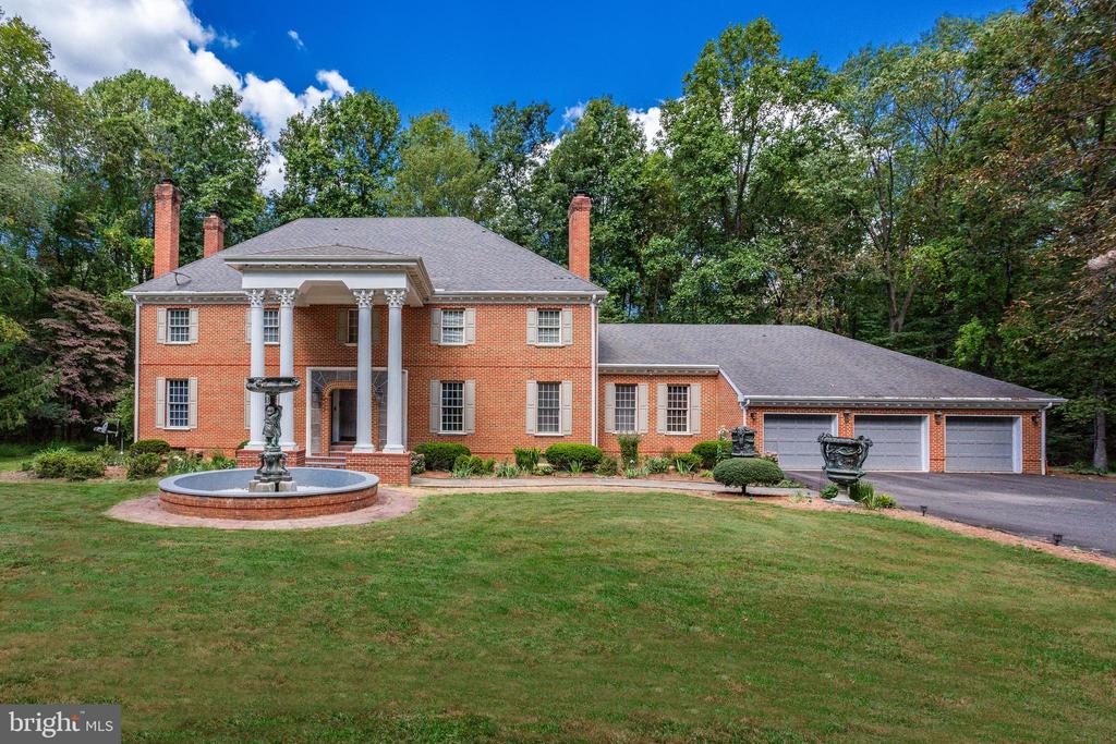 Quiet 5 Acre Gated All Brick Estate. Langley HS District. Custom built colonial with Corinthian Columns. Lavish details throughout: Special decorative stone made of fossil stone tile in the entrance, European tile flooring, elegant moldings, Harrebone Laid hardwood floors, whole house central vacuum system & much more. Must see features list! Formal living room & dining room. Remodeled kitchen with 2 ranges, Sub Zero refrigerator, granite counters, all new lighting plus wood fireplace with matching granite surrounding. Light filled sun room with new windows & French double doors accessing the cozy Family Room with fireplace. Library with fireplace. Upper level feat; master suite with grand bath plus 3 bedrooms, hardwood floors throughout. Fully finished walk-out lower level with huge rec room & exercise room. Gorgeous deck backing to trees - perfect to relax or host entertain 4 car garage with new full HVAC system.