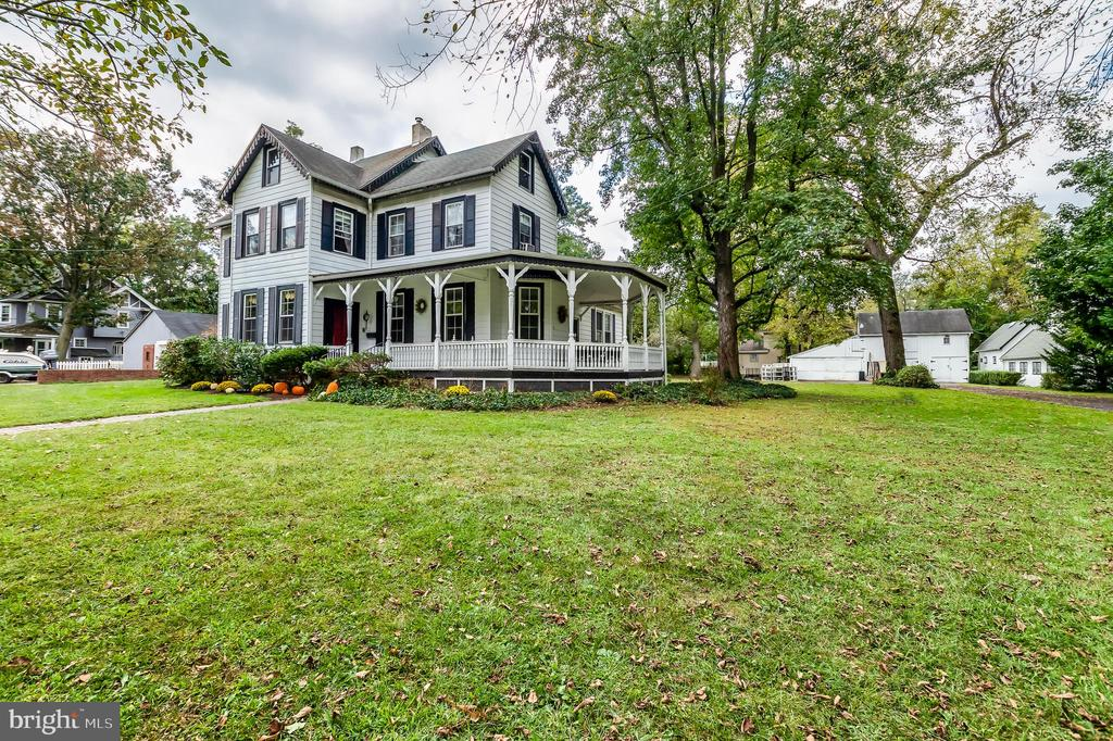 Rare opportunity to own an 1800's Victorian nested within an exclusive enclave of homes that has a long view of the Delaware River from the wrap around porch. This stately home, in the much desired Burlington Twp. School System, is largely worry free giving you a move-in ready home to make your own. A brick pathway leads you to a covered wrap around porch that is approximately 49' x 9' for afternoon lunches and evening cocktails. A stately Foyer awaits as you enter the front door. The elegance of high ceilings, crown molding, and gleaming original plank hardwood floors w/hand-forged nails and wide baseboard moldings grace every room. An original stair case curves around to the upstairs. You make your way from the Foyer into a fabulous great room where guests were received and entertained, a mantled fireplace is the focal point of the room. A formal dining room replete with a sparkling chandelier, leaded-glass built-in server cabinet offers enough dining space for large family or formal dinners. There is a back stairway nestled behind the dining room to the second floor. A 24' x 17 family room with beamed ceilings, gas fireplace and windows that lookout onto a large back yard, is 408 sq. ft. of infinite uses. The family room also has an entrance to a library/office with plenty of bookshelves. The Kitchen as plenty of oak cabinets, recessed lighting and space. The laundry/mud room also has a full bath with a walk-in shower that saves trapesing through the house after working outside. Upstairs, on the second floor, there are four bedrooms and two full baths with tub-showers. There are two bedrooms that adjoin which would serve perfectly as a nursery or dressing room. There is a generous landing which can serves as an additional room space, perfect for an office area. From the second floor, there is a staircase leading to two additional bedrooms/playroom/storage area. There is also a walk-in cedar closet in addition to a half-bath. Now to the nuts and bolts: Home is being sold in as-is condition. Not in a flood zone. The family room added in 1968; Updated plumbing 1968, including sewer line to the street; Kitchen, mudroom/laundry and bath were renovated 2006; All new whole-house electric wiring w/panel box in 2007; Vinyl replacement windows, installed in 2005; Though heated with oil (with an above ground tank) Gas is available in the house. Heater was installed in approx. 2006; Water Heater installed in 2017. Roof is older, but is sound. Bathrooms are dated, but in great shape. Basement is dry. INCLUSIONS: All area rugs, window treatments, contents of second story of garage/outbuilding and a John Deere Riding Mower! Home has winding and sometimes narrow stairways. Please use caution. This home reflects the distinctive taste, quality and craftsmanship of one of the greatest eras and it could be yours!