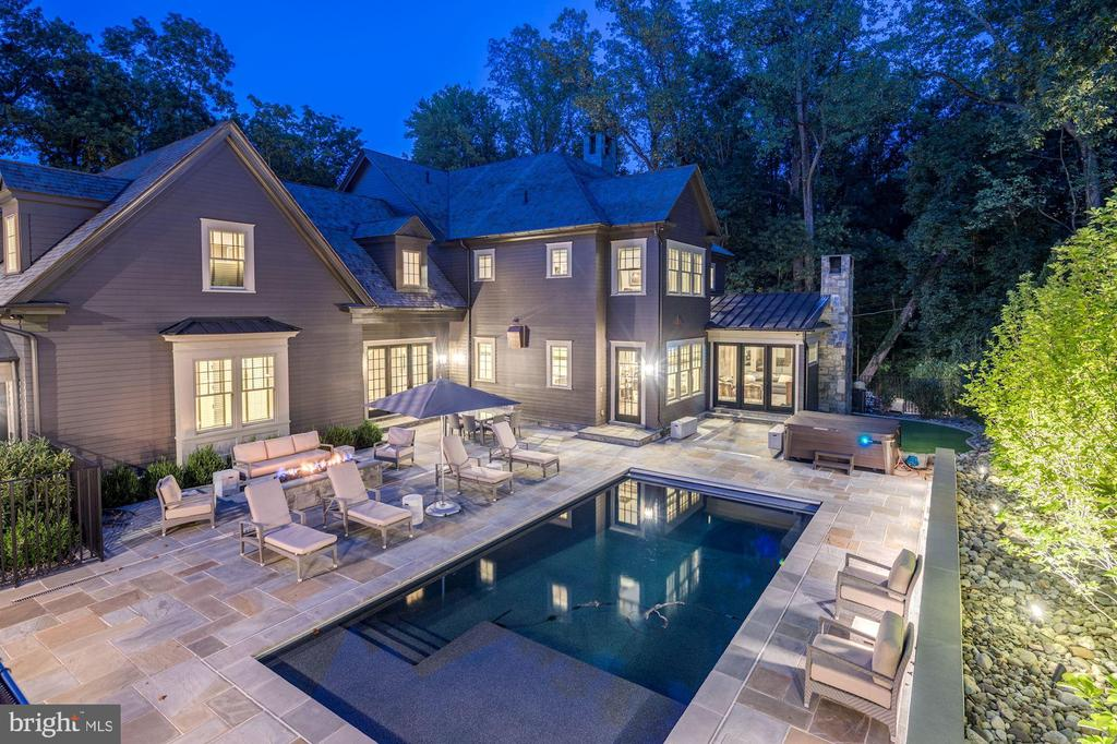 Welcome to 6800 Bradgrove Circle! Nestled away on the fringe of the city is this one-of-a-kind, luxurious, custom-designed home in one of the most sought-after areas in Bethesda. Spanning over 10,000 square feet, the main home boast six bedrooms, six and a half baths, and a separate 900 square foot guest house above the detached garage. Every detail was carefully selected and expertly crafted. Timber from the property was sent to a mill for repurposing to be thoughtfully incorporated back into the home. The main level boasts an open floor plan with an abundance of natural light, a formal dining room, two fireplaces, a private sitting room, and a secluded home office with custom-built ins. The kitchen has world class appliances, two large islands perfect for entertaining or dining in, a butler~s pantry, and plenty of storage. There are two dramatic stairways and a custom elevator, which leads you to the private bedroom suites, all boasting sleek en-suite baths, generous closets, and wonderful views. The lower level features a host of amenities including a full-size wet bar, home theater, a well-equipped fitness area, a custom Browning walk-in safe, private bedroom, and full access to the oversized yard. Not to mention the outdoor living space - a main level balcony overlooking the yard ideal for morning coffee, a lavishly crafted saltwater pool with custom hardscaping, a jacuzzi, an outdoor bar area fully equipped with a built-in grill, fridge and TV ~ this backyard was designed for entertaining! No expense was spared when creating this architectural masterpiece!