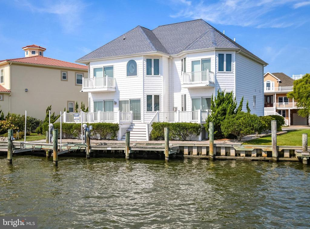 Luxurious direct waterfront living with breathtaking Bay Views. This 5BR/3.5 BA Waterfront Single family home is in Heron Harbour Isle. This beautiful home overlooks the Bay and comes with a deeded boat slip with lift, and vinyl bulkhead.  Share precious family time watching magnificent sunsets from the family room and enjoy the warmth of a fireplace for year around enjoyment.  The family room has a wet bar and is a perfect place to entertain family and friends. There is a glass slider and a wall of windows to optimize all the water views off both the family room and dining room. The large kitchen has granite countertops and plenty of cabinet space to delight the chef in your house.  There is an incredible waterfront deck for outdoor grilling and crab feasts.  The spacious waterfront master bedroom suite is on the first floor and has a master bath with shower and jacuzzi tub, walk in closets and a sliding glass door leading to a deck with incredible views overlooking the Bay.  As you go up the stairs you will immediately feel like you are in the Caribbean with all the bright colors and themed rooms. There is a second family area or office area with a balcony overlooking the water. The second floor also has a beautiful second bedroom overlooking the water with its own private balcony.  There is a Jack and Jill bath connecting the second and third bedrooms, and the fourth and fifth bedrooms also share a Jack and Jill bath.  One of the many highlights of this home is the awesome decks and balconies.  Use them to relax, listen to the water, watch sunsets night after night, and enjoy the boats as they go by. This home has many upgrades throughout, including 40 year shingles, heated tile floors, two car garage, finished bonus area over the garage,  2X6 construction on exterior walls, upgraded lighting, upgraded landscaping, and 2 zone heat with gas on the first floor, heat pump on the second. floor. Imagine yourself in this beautiful home  in one of the nicest communities in Ocean City.  Heron Harbour Isle is amenity rich with two outdoor pools, an indoor pool, a kiddie pool, fitness center, social room, sauna, locker room, two Har-Tru tennis courts, sidewalks and piers.  Enjoy your boat, fishing, crabbing, kayaking and paddle boarding all directly out your back door.