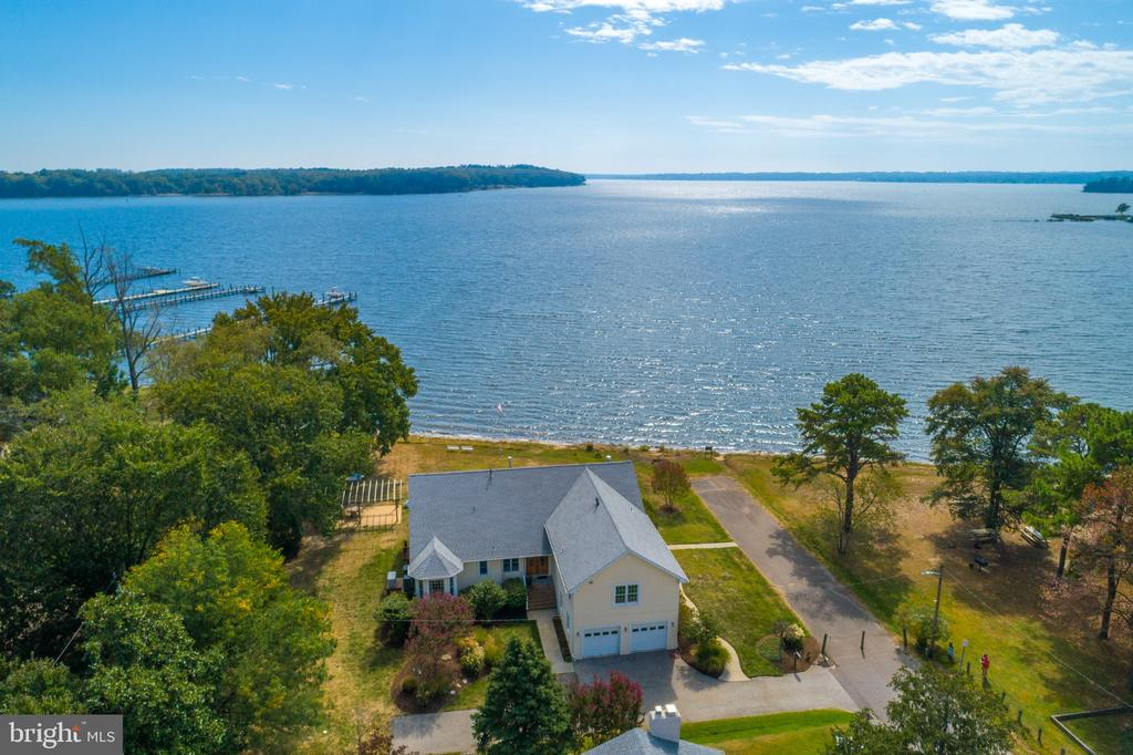 "Enjoy breathtaking views of Sillery Bay on the Magothy River! Custom designed open floor plan with 10' ceilings built in 2005 along 180' of non riparian waterfront. Whole house has been freshly painted and extremely well maintained. Stunning master bath has 6' Jaccuzi tub, glass shower with 4 nozzles & 3 body sprays, radiant heat on Prog Thermo under C-tile. Its gourmet kitchen is the focal point of the great room and is equipped with 2 Blanco sinks, Grohe fixtures, granite counters, RO, 48 SS stove with 6 gas burners & griddle, 2 electric ovens, hood with warming lights, shelf & pot filler. Self contained and fully equipped au Pair suite on second level. Gorgeous sunsets can be viewed from its private T-Tech deck. Floor coverings include 5"" wide hardwood floors and porcelain tile. Tray ceilings with cove lighting in dining room and master bedroom. Oversized 2-car garage with workroom, 60' of T-Tech front deck, 30' electric awning, 25'x15' covered patio adjacent to deck, Rinnai, 12'x18' barn style shed with 2 lofts. Well has constant pressure pump. Find all this situated on approx. 2/3 acres of level homesite with sandy beach."