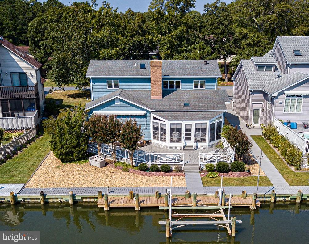 """This waterfront home is absolutely striking - with the very wide open spaces of the entire home, which are enhanced by the sunlight soaring through the many skylights throughout the house, and highlighted by the gorgeous wood accent walls. Located on a deep canal with boat dock and lift, very quick access to the Isle of Wight Bay and St Martin river, high elevation and no bridges. Wonderful updated kitchen with Corian countertops, stone back splash, stainless steel appliances and beautiful cabinets. Amazing entertaining space, with huge living/dining room and also a cozy beautiful family room w/fireplace, both leading to the open kitchen and breakfast nook -- which then lead to the large bright sun room, which then opens up to the large waterfront deck. The first floor waterfront master has a walk-in closet, a gorgeous updated bathroom with handsome tiled shower and dual sinks, and sliding glass doors that lead out to the morning sun room. There is a second bedroom on the first floor, currently being used as an office. The open view of the entire house as you walk up the stairs to the second floor is spectacular, as you take in the beauty of the wood and the rays of sunlight through the windows and skylights. Upstairs there are 2 more waterfront bedrooms (plus a """"hidden room"""" for extra guest sleeping space or easy storage) and a full bath. This is the perfect home for family and friends, with so much space for casual living or gracious entertaining, and 10 ceiling fans to give you that cool beachy feel. Utility room with sink/washer/dryer and more storage, leads out to insulated garage with attic storage. This home has been loved and very well maintained by current owners for many years.  The Ocean Pines community includes 5 pools (one of which is indoor and one of which is OC beachfront), a golf course, a racquet sports complex with pickleball, tennis and platform tennis, 10 parks, many walking trails, fishing ponds, boat ramps, kayak and SUP rentals, marinas, dog """