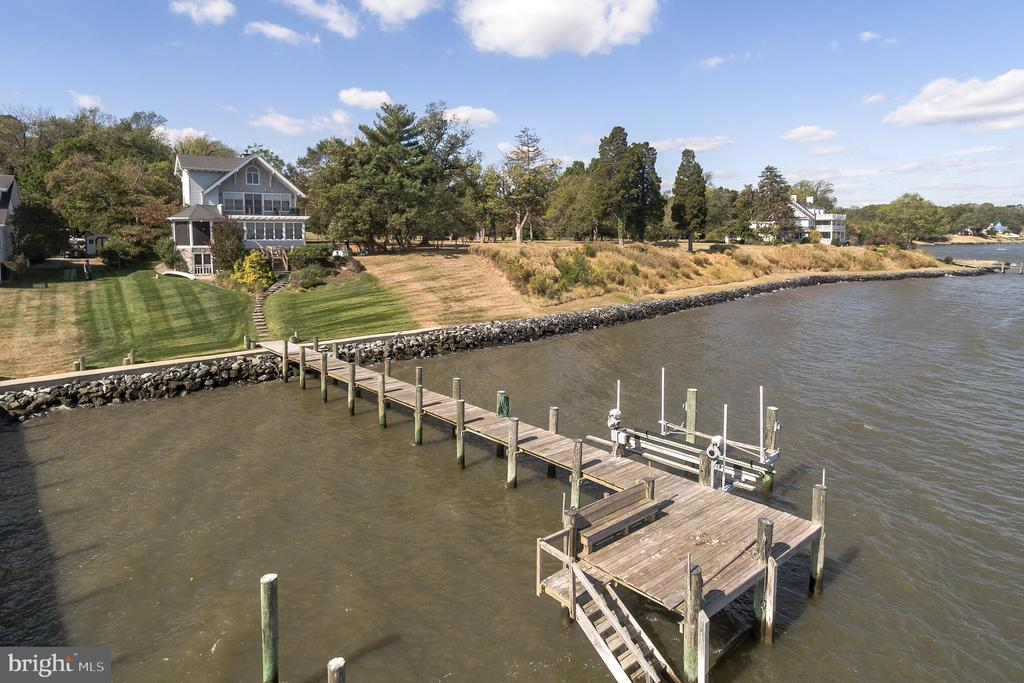 Your search is over for the perfect waterfront! Gorgeous Chesapeake Bay views with your own private pier and lift. Easy access from deck or the basement! The house was rebuilt in 2007 with the highest quality standards. Here you will have the main level with gorgeous kitchen and walk in butlers pantry, formal dining room, a library/bedroom with full bath next door and magnificent living room and sunroom all with Spectacular Bay Views! Huge deck off the living room and private screened porch allow you enjoy the bay breezes throughout the year. Upstairs you have a wide staircase to ascend to the bedroom level with 3 bedrooms, full bath with steam shower and master suite and beautifully appointed master bath. One bedroom has it's own private deck for out of this world views. Striking architectural details are seen from the decks along with architectural shingles, wood trim and Hardy Plank siding. Go up another level with still more views from lots of windows to the bonus room which is lined with cedar closets for storage. Unlike most waterfront homes, here you have a full unfinished basement for storage of your watercraft and household items. It is a walk out to the steps down to the pier. So many upgrades are found in this beautiful home including, irrigation, extra lot was purchased giving you more land and frontage with no easements. All the floors are heated with radiant heat , steam showers, jacuzzi tubs, skylights, wood floors, walk in pantry, pocket doors, built in book shelves, kitchen features wine cooler, espresso maker, double ovens, 6 burner stove, prep sink and large deep stainless sink, utility room with sink and extra refrigerator, 2 generators, water softener, UV light and reverse osmosis, Weather resistant Anderson windows and so much more! So much charm, so many unobstructed views, only 12 years new and situated next to a very large parcel of land with the only house far, far away from yours. Privacy and Bay Frontage are very hard to come by! Blue Rib