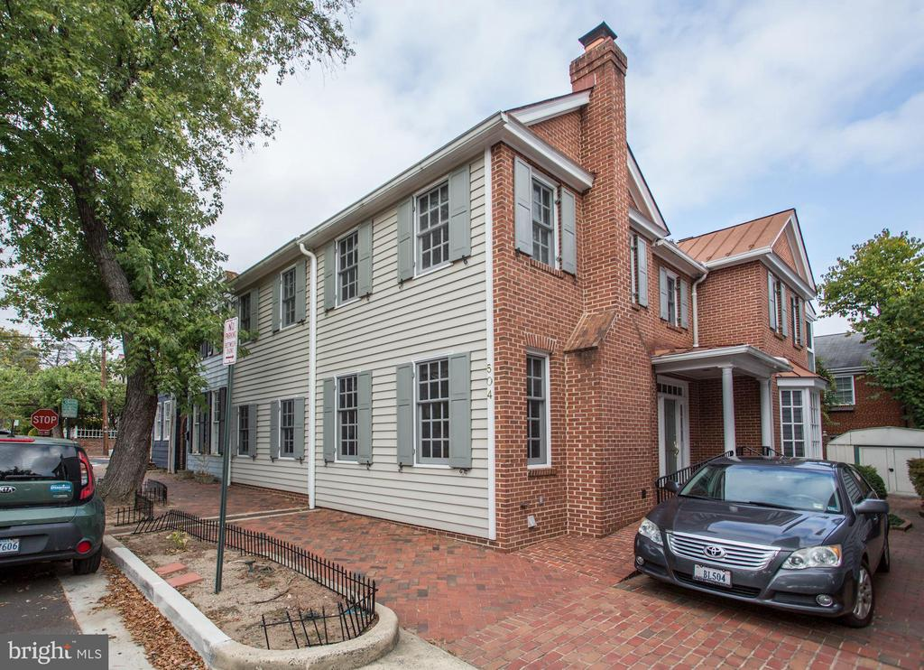 Unique double lot townhome on the south side of Old Town Alexandria, close to a grocery store and across the street from a park. The home has been in the same family for over 100 years. This home is made up of 2 unites that have been combined into one and also has off street parking that could be made into a garage. It is very hard to find a home of this size in Old Town at this price. The home has an elevator and is set up with lots of handicap assistance and capabilities, including handicap baths on the main and upper levels. Main level has a side entry with a ramp, as well. Entry into the foyer, to the left on the street side, you will find a large living room, to the right is the family room with a large prick fireplace and bay window to the side. French doors on both sides of the fireplace lead to a covered porch and the courtyard behind it. Off the family room you will find a mudroom, kitchen with stainless steel appliances and natural cherry cabinets, gas cooktop. Large enough for a kitchen table and walks out to the courtyard. Off the living room you will find the formal dining room with large window to the street and a tray ceiling. To finish out the first floor, you have a large powder room that is handicap accessible, the elevator, and the stairwell. As you go to the upper level, you will find 3 huge bedrooms and an office that could easily be changed back into a 4th bedroom. It is currently being used as an office off the master. The master also has a covered porch off the back overlooking the patio and garden. There are two baths on the upper level as well. The lower level is only ~ of the townhome. There is a rec room, a bar, laundry. And utility room on that level. The elevator accesses all 3 levels, as well.  In the rear yard, you find a brick patio, a grassy area, garden and a storage shed on the side of a brick driveway that allows for one or two off street parking spaces. Location is always so important and this home is sitting so close to the mai
