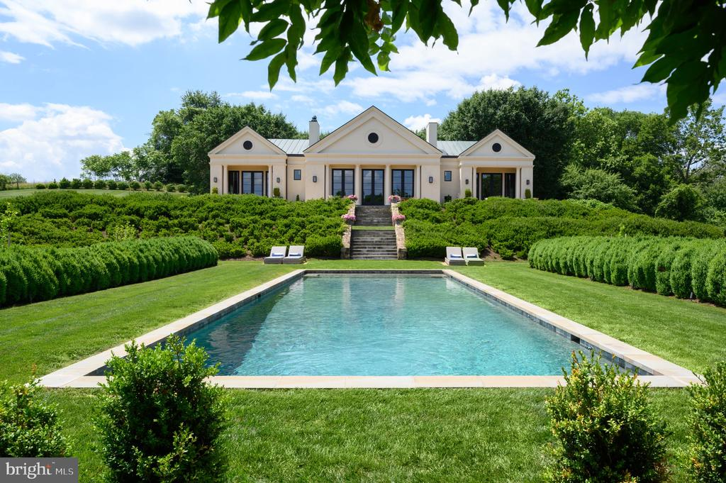 Set on an idyllic five-acre parcel, bordering a 400 acre private estate, this extraordinary Neoclassical Palladian villa offers over 6,000 square feet of interior living space and spectacular views of the iconic Blue Ridge Mountains. Originally built in 1997 by esteemed architect Errol Adels, Sageview finished a two-year complete renovation in late 2017. Inside, a magnificent Great Room includes the gourmet kitchen, dining room and two seating areas that overlook the terrace and swimming pool. Each of the property's five bedrooms - including two large ground level master suites - offer ensuite baths clad in floor to ceiling Carrara marble. Additional noteworthy features include an indoor/outdoor Sonos sound system, 10' custom doors, custom oak cabinetry, Miele and Sub-Zero appliances, Italian marble countertops, Lefroy Brooks fixtures and sconces, reclaimed wide-plank flooring, and custom millwork throughout. The 1,225 sqft. guest house features a spacious entertaining space with a concealed full kitchen, large bedroom and ensuite bath.