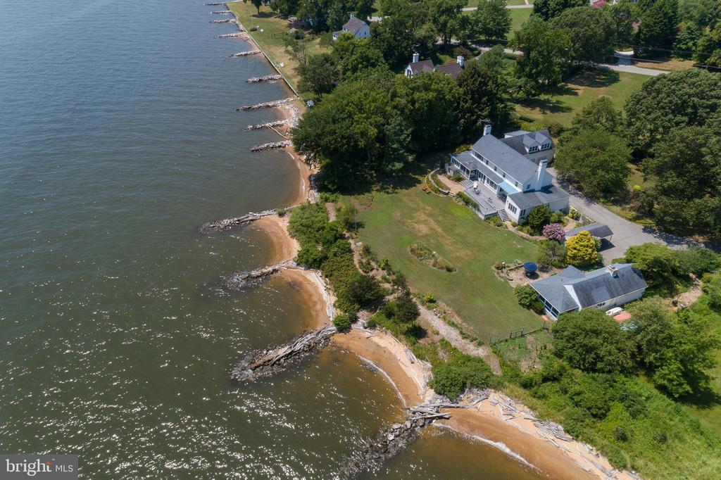 Incredible opportunity to own a family compound! Waterfront double lot on the Chesapeake Bay! Main house w/views of the Bay from the Living Room, Dining Room, Kitchen & Sun Room. 1st floor Master Suite. 2nd floor  Master Suite & 2 additional en-suite Bedrooms also enjoy Bay vistas. Indoor jetted pool, Study, 2-car Garage w/1 Bedroom Apt above. Large Deck, screened porch & sweeping lawns. Private 1 Bedroom Cottage w/FP & screened porch. Private location yet just a short stroll to the fresh water Lake, The Point & the Club House. Conveniently located, private 24/7 gated community 30-45 minutes from Baltimore, 90 minutes from Washington & just 20 minutes from Baltimore Washington International airport.