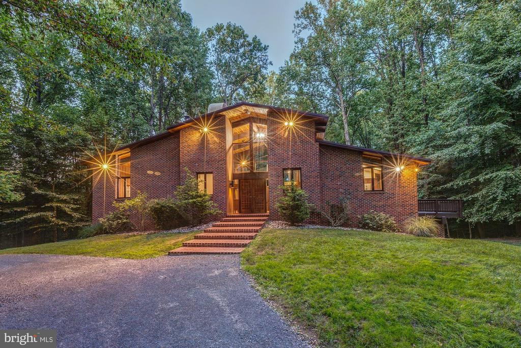 Privacy and tranquility abound in a pristine 5-acre forested setting in Great Falls. Soaring trees provide the natural backdrop for this stunning custom Acorn Deck house that impresses immediately upon entry. 23~ cathedral ceilings reveal walls of windows to fill the welcoming great room with light and offer a view into the gorgeous surroundings that lay beyond the dual sliding doors onto the custom decking. A massive brick fireplace stretches from the hardwood floors to the planked ceilings, showcasing the exquisite craftsmanship that went into creating this artful residence. The gourmet kitchen, formal dining room and sunroom all connect to the great room, each with its own unique setting and views out into nature. Soak up the light each morning in the sunroom, the perfect place for coffee, tea and relaxation. Large windows in the kitchen provide light and brightness, and state of the art stainless appliances are a chef/entertainer~s dream; the dining room offers ample space for a large table and convenience with the connected floorplan. Adjacent to the great room is the master suite with a three-story wall of windows and a double-sided fireplace, offering every amenity the discerning homebuyer demands, including a stunning view into the forest. The suite also overlooks the indoor saltwater pool, with a convenient and elegant spiral Mahogany staircase leading directly from the bedroom down to the pool deck. Heated for your convenience, the pool offers year-round relaxation and enjoyment. An exceptional master bath with luxury finishes completes this one-of-a-kind bedroom suite, one of the showpieces of this remarkable home. Downstairs are two additional bedrooms, both large in size, with a full bathroom and steam shower. From the lower level, the 5-acres of natural wonder are accessible via walk-out patio to experience the grounds, and a wood burning fireplace provides ambience and warmth in the colder months. With over 4,000 square feet of luxury living space, this custom home is unrivaled not only in setting, but also with its signature design, aesthetic and appeal.