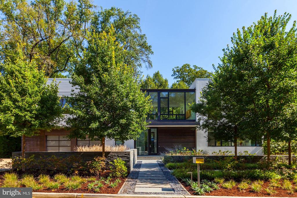 This stunning contemporary designed by renowned architect Robert M. Gurney is an exquisite masterpiece. To complement the architecture this residence was chosen to be sited by its thoughtful owner on sought after Hampden Lane in the desirable Bethesda neighborhood of Edgemoor. The beautiful custom finishes include floor-to-ceiling insulated glass windows, maple flooring, aluminum stairs, walnut millwork and Spanish cedar. The custom floor plan flows seamlessly from the welcoming two story foyer into the dining room, living room, kitchen and breakfast room. All of these rooms open to a wrap-around deck, swimming pool, spa and custom landscaped garden. A few steps toward the back of the main hallway an inviting family room and screen porch welcome the outdoors in. The main level includes a custom walk-in closet/mudroom and powder room with gliding pocket doors leading down the hallway to an oversized 2 car garage. In the main foyer the floating aluminum and glass staircase guides you effortlessly up to the second level where a welcoming second living room/family room overlook the front and back gardens. The master suite is composed of the master bedroom, the master sitting room/alternate 5th bedroom and master bath which all echo the fine finishes found throughout the entire home. The second wing of the second story provides another three spacious bedrooms, 2 full baths, more than ample custom closets and a large spacious laundry room. The lower level of the home continues in its architectural splendor to guide you to the full service exercise room in opaque glass. The lower level recreation/game room includes a powder room, huge storage closet and guest bedroom with full bath. High ceilings throughout all three levels, custom lighting and sound, professionally designed landscaping and stone work complete the fine finishes of The Gurney Glass House. A total of 5-6 bedrooms and 4 full baths with 2 powder rooms. A once in a lifetime opportunity to own a masterpiece.