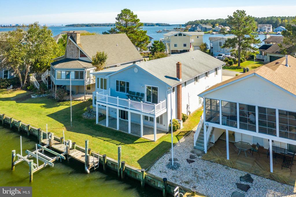 This lovely waterfront home in Ocean Pines offers five bedrooms, three and a half bathrooms, an oversize two car garage with large paved driveway (6 car) and lots of living space. It conveys furnished with few owner exceptions. This gorgeous waterfront home is situated on the basin of several wide canals with a beautiful view of the surrounding waterways and direct access to the open bay. Do you like to golf?  Strategically located, the home is only a few blocks from the Ocean Pines golf course. Interested in entertaining? The home offers plenty of room on both levels for family and friends. The upper level includes sight lines from the kitchen into both upper level living rooms, the dining room and waterways. Additionally there is also a large upper level Florida room with direct water views. Conveniently located in the upper level dining room behind cabinet doors you will find a full size washer and dryer. Open the slider to your large deck located just off the family room on the upper level and enjoy refreshing bay breezes as you sip your morning coffee or enjoy a glass of wine. Wave to the boaters as they glide by. The upper level also offers a large master bedroom with a striking marble slab and glass door shower ensuite. The upstairs includes two additional bedrooms, a queen and two twins. Both the upstairs master and queen bedrooms have peek-a-boo bay views. You will also find another full bathroom upstairs including a tub. Circle down the spiral staircase to find a comfortable king bedroom with direct water views. Also a spacious queen bedroom that shares a handicapped accessible Jack and Jill bathroom. There is also a convenient powder room and stack washer / dryer downstairs. The lower level bathroom has been designed for handicapped accessibility. The lower level includes a family room and a Florida room, both with direct water views and a toasty warm fireplace for chilly nights. The TV~s featured in almost every room of the house convey. Open the downstairs family room slider to enjoy the lower level patio, dock and boat lift. Interior features include easy care wood and tile flooring, lots of windows for natural light, upgraded kitchen cabinets, granite countertops, built-ins, crown molding, tiled showers and much more. Mechanical features include cost saving two zone HVAC, electric baseboard heat, 2 gas fireplaces, a tank less hot water system and refrigerators on both levels. Ocean Pines has been named Forbes number one place to retire in MD for 2019. Waterfront living doesn~t get much better as Ocean Pines amenities are unrivaled offering multiple outdoor pools, an indoor pool, a beautiful new yacht club and a beach club with pool, volleyball and bar service. Ocean Pines also offers tennis, golf, marinas, parks and walking trails. The area is a golf mecca. The Pines also has close proximity to Ocean Downs racetrack and casino, Starbucks, outlet shopping, Assateague and more. Come live the good life on the water in this well maintained Ocean Pines home.