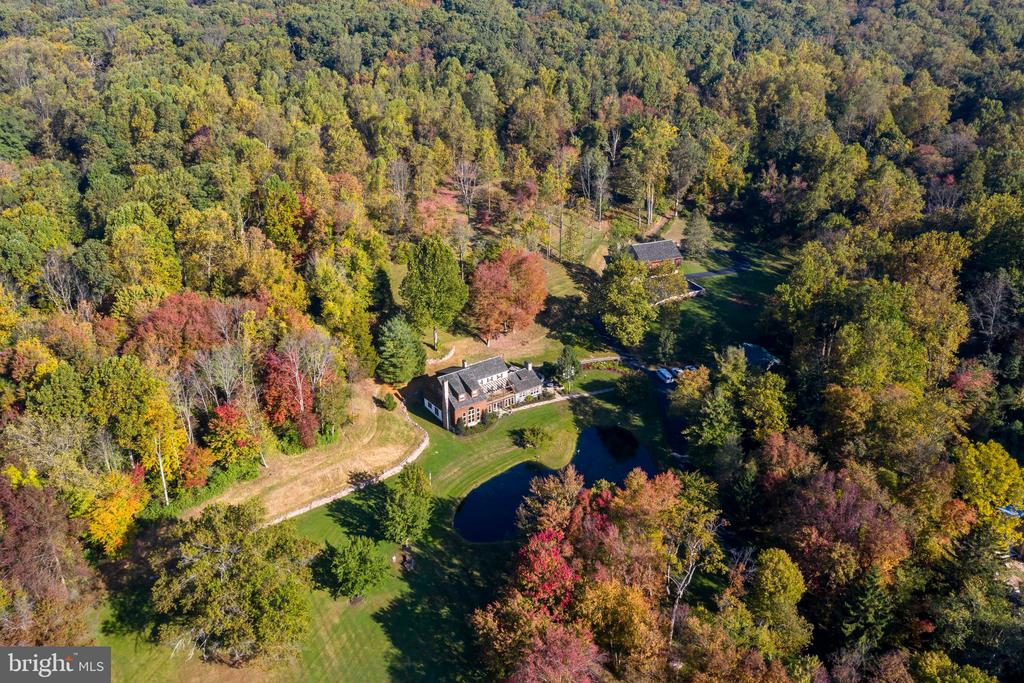 Unparalleled views, impeccable landscaping, and pure serenity awaits you at 141 Hopewell Rd. A meandering drive carries you past a spring-fed heart-shaped pond to an incredible 23.5 acre estate with a 5000+ square foot residence, bank barn, spring house and detached garage that backs up to French Creek State Park and Game Lands totaling over 7000 Acres. Originally owned by Thomas Potts with deeds dating back to the 1800s, the original stone farmhouse was rebuilt and expanded with newly constructed country contemporary log and Dutch lap additions in the late 1980s. Located near the headwaters of the west branch of French Creek, boasts all the finishes one should expect in a quintessential Chester County farmhouse: wide pine and handmade tile floors, antique wood beams, hand-hewn log mantels, and exposed stone walls, while also having an impressive layout conducive to the modern buyer. A flagstone walkway leads to a central solarium entry with a wall of French doors and Banta ceramic tile flooring that opens to a family room with stone fireplace and spiral staircase to a 2nd floor loft. The tile flows into a generous log cabin style kitchen with brand new granite countertops and appliances including an induction cooktop and steam convection oven, brand new granite countertops, plus a breakfast nook and access to the 900+sq ft stone patio and functioning spring house with arguably the most delicious water in the county! The kitchen is open to a spectacular dining area with remarkable walk-in fireplace and vaulted ceilings. Flanking the solarium on the left is a dramatic 18' two story living room with floor to ceiling stone fireplace and enormous Palladian window that floods the room with natural light and offers incredible pond views! Finishing out the first floor is an oversized office with custom bookcase, mechanical room and powder room with pedestal sink. An open wood staircase from the living room leads to the master bedroom suite with large walk-in closet, and masker bath with access to a 2-tier deck with hot tub and expansive wooded hillside privacy. The master landing also provides access to a convenient laundry room, loft area and a large front facing deck. The 3rd floor has a princess suite with exposed stone wall and wood beams and a 17x10 multipurpose loft. Two additional bedrooms with ample closet space and a hall bath with Corian counter complete your interior living spaces. Outbuildings consist of a 2-car detached garage with two office rooms and a half bath, perfect for an at-home business, as well as an impressive bank barn that was fully rebuilt on the antique frame with countless uses. Low-maintenance intelligent landscaping has been thoughtfully executed to ensure that you can spend your days enjoying the beauty instead of weeding your gardens. Every hunter dreams of owning a place where they can manage habitat, fiddle with gear, scout to their heart~s content, and hunt without asking permission... this is that reality!  If you have an appreciation for meticulous attention to detail and undeniable uniqueness, make a move on this once in a lifetime opportunity!