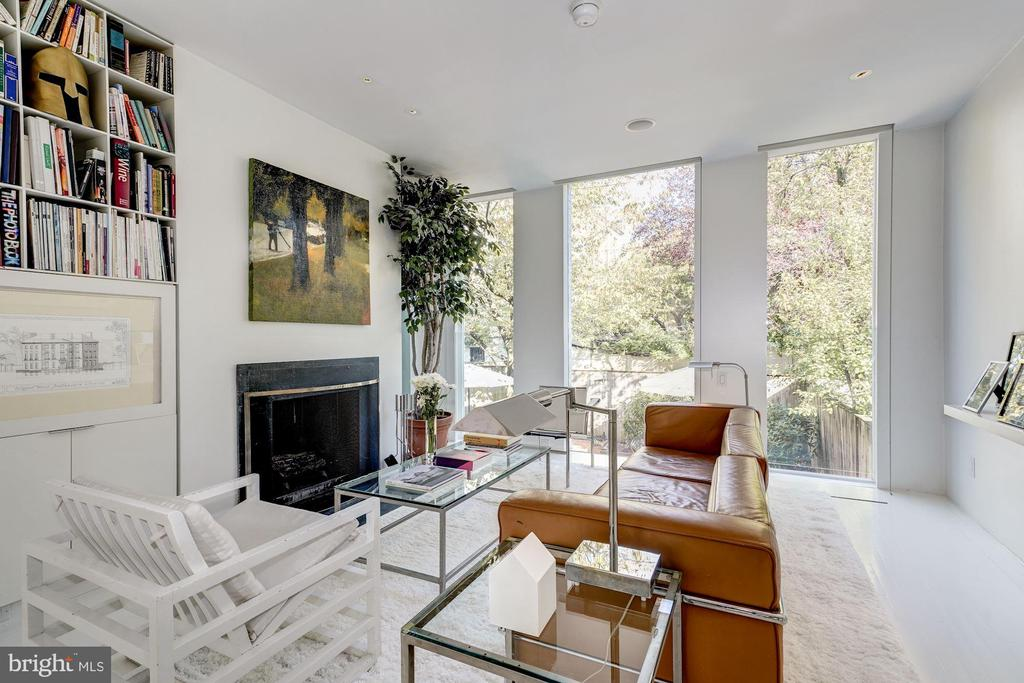 On a historic, tree-lined street in the heart of Georgetown sits an impeccably renovated Greek Revival-style white clapboard home. Built in 1863 as an end row house with a contiguous twin, the property has since been combined into one large dwelling with three to four bedrooms and three and one-half baths by architect and owner Simon Jacobsen. Featured in Architectural Digest, the 3,234 square foot home is also the recipient of the 2010 AIA/DC Washingtonian Award. A front door with transom windows leads to a formal hallway with three soaring closets. Rounding the corner, a large and open gallery is revealed, suitable for entertaining. Old plank floors have been finished with a glossy white porch paint, lending to a theme concurrent throughout the home of white-on-white luxurious minimalism. Three steps lead up to a grand living room with giant custom floor-to-ceiling windows. Adjacent is an open library with fireplace (one of five in the house), towering bookshelves and sliders out to the rear deck. As with many homes of the era, cooking is done at the below-ground level. Full-height doors and lowered handles create the feeling of high ceilings, with natural light coming through six-over-six pane windows with white plantation shutters. The thirty-foot long catering-style kitchen designed by Jacobsen Architecture features Vermont green slate floors, a white Corian counter running the length of the room, custom LDF cabinets, pull-out birch trays, professional grade fixtures, and a large pantry. Appliances include a Five Star four-burner gas range, LG side-by-side refrigerator and Bosch dishwasher. Next-door is the dining room with green slate floors plus a fireplace, as well as sliders out to the two-tiered rear garden. Also on this lower level is a powder room, laundry, media room with brand new Master Stain Black carpet and a wonderful office with brick floors, built-ins and oversized windows. Main sleeping quarters are on the third story, with new Berber carpet and synthetic padding throughout. The spacious owner's suite features a wall of massive windows with a full-length automated Lutron shade. Enjoy a large private dressing room with windows and custom built-ins! The en suite bath features white Carrara floor tile and a Jacobsen-designed vanity with Corian countertop and recessed round sink with Dornbracht fixture. The white-tiled Dornbracht walk-in shower has an oversized rain head and chrome wand. There are two more nice-sized bedrooms at this top level, each with a pair of six-over-six pane windows, tons of closet space and a light, airy feel. Two full baths are off the hallway, with Travertine floor tiles and recessed halogen lighting. One has a marble vanity top while the other is Corian. Each has a shower/tub combo. What is currently the dressing room in the owner's suite could easily be converted back into the home's fourth bedroom. An incentive of merging two homes into one is the additional amount of private outdoor space. Multiple exits lead to a large fenced-in, rear garden edged with mature plantings. An additional balcony with spiral stairs overlooks the backyard oasis with its garden and small built-in pond and fountain. It's the perfect place for dining al fresco or entertaining friends. Also of note is a private parking pad with space enough for up to three cars, along with monitored ADT security on doors and windows and dual-zoned HVAC system.