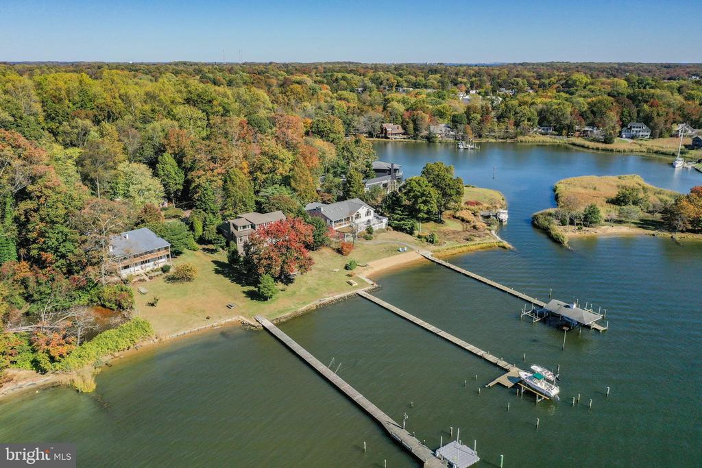 BACK ON THE MARKET!  Unsurpassed views of the South River with a quick boat ride to the Chesapeake Bay. Your own sandy beach. Covered boat slip which is no longer available. 3 additional slips make this exciting property your own private playground. Located at the end of a cul-de-sac, This custom home is surrounded by extensive hardscape with Belgian stone edging. A welcoming 6 ft wide walkway of Pennsylvania blue stone slate leads you to a large covered front porch with blue stone slate floor & a cedar ceiling. Huge covered back porch/deck with mahogany wood floor & cedar ceiling is easily converted to a screened in porch or garden room. Nautical stainless steel cable railings give this home that special coastal feeling. Bluestone slate also on walk ways to pier and waterside porch. Huge pergola covers the stone patio with mosaic insert. Enter through a limestone foyer. Be wowed by the stunning views out massive windows.Cedar ceilings in the main rooms. See all the way across the South River to Selby Bay and Turkey Point. Open floor plan features a library/music room separated from the great room by large columns. Built in display shelves with special lighting and a stone(gas) fireplace with large re-claimed wood mantle adds to the ambiance of this picturesque interior. Additionally there are hardwood floors. The gourmet kitchen also showcases the incredible view and backyard family playground from the huge palladium window. Ceramic floor, Mexican tile, natural solid cherry cabinets,(tongue & groove) extra large island for food prep and entertaining make this a real cook's kitchen. Main level master with additional Palladium window brings the outside in. An outside exit on the side brings another spot to have your morning coffee. Two additional bedrooms on the main level, and one of two laundry rooms---the other one is in the lower level to accommodate the 2 bedrooms and full bath with outside entrance so your guests can come in from sun and fun and shower without 
