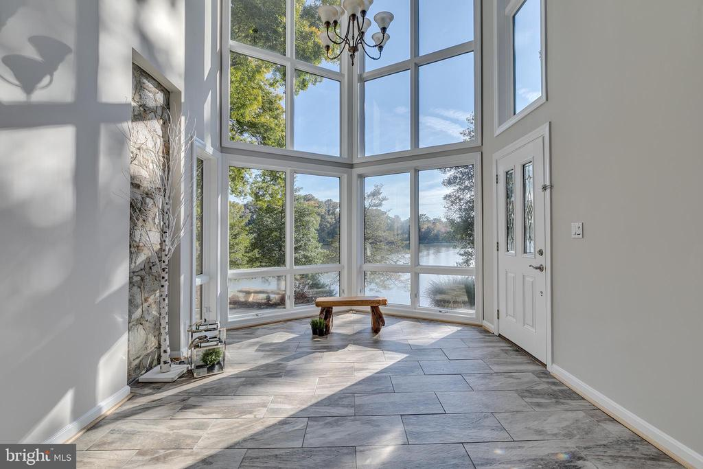 Open the door to Serenity. Located at the end of the Severna Park Yacht Basin your private retreat awaits.  Perfectly placed at the heart of Forked Creek rests this stunning home that melds quality craftsmanship with modern luxuries.  Breathtaking water views greet you as soon as you drive through the gate and see the stone and wood home nestled on over a half acre lot. Step inside into the 2 story foyer with floor to ceiling windows. The Great Room provides ample space for relaxation and entertaining and is designed to maximize the views from every seat.  A 19' wall stone fireplace adds a cozy vibe while windows facing the water showcase expansive views and allow access to the outdoor sanctuary. The large updated kitchen was renovated in 2017 and features a beautiful solid tongue in groove wood ceiling with exposed beams. This bright and spacious kitchen with gorgeous views of the water has so much to offer you may decide to never leave. There is a massive central island, stainless steel appliances, granite countertops with huge breakfast bar, eat-in kitchen area as well as a sitting area. Beside the kitchen is a large walk in pantry, a mud room and lovely butlers pantry with side entrance that takes you right to the driveway. Connected to the kitchen is a cozy sitting room with stone fireplace, bar area, access to basement, powder room and cut through back into the great room. The majestic owners suite is anchored by a whole wall stone fireplace on one side and two french doors that open to a private balcony on the other.  The balcony spans the length of the master and with 180 degree views of beautiful scenery, overlooks the pool, patio and river. There is an additional side entrance leading directly to the pool and pool house. Prepare for your day in comfort with luxurious dressing room and large closet with custom storage system. The master bathroom has heated marble floors, large soaker tub, separate walk-in oversized shower, and double sinks. The entire maste