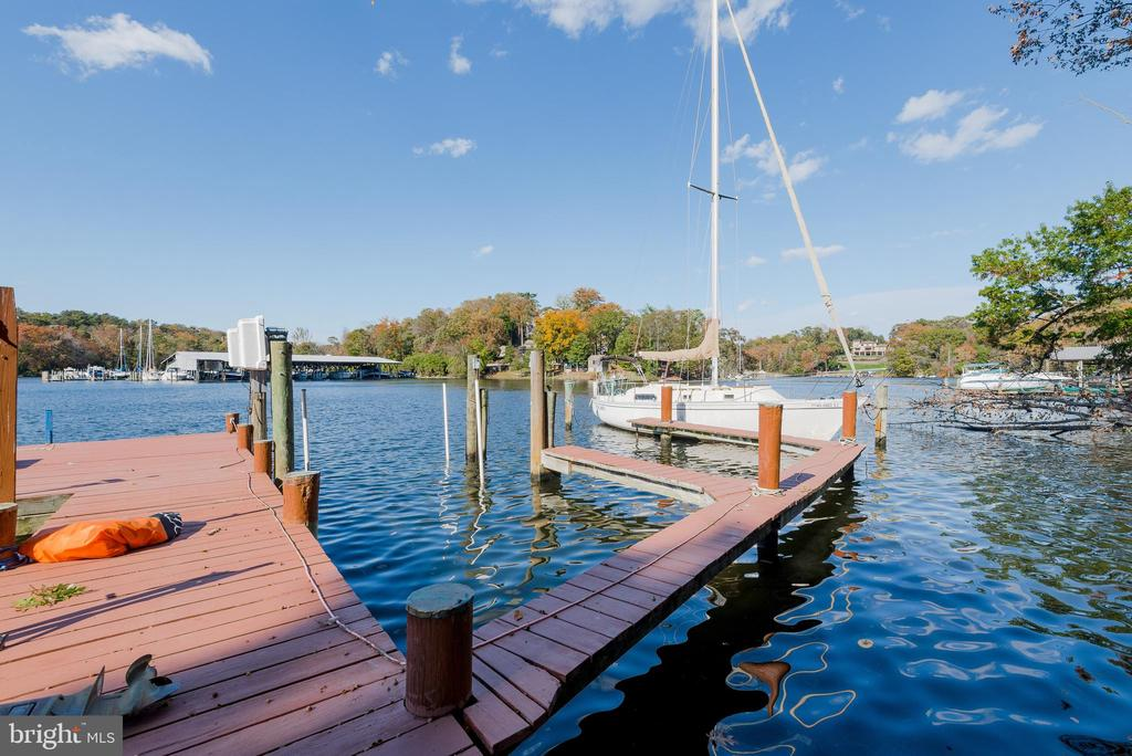 BOATERS DELIGHT. Enjoy the multi-slip, deep water private pier for kayaking, paddle-boarding or canoeing  on a protected cove. This sunlit rancher with 4 bedrooms and 3 baths has a wall of windows framing an expansive WATER VIEW! For the car enthusiast  a 2 1/2 car garage with a large work shop space. A large screened-in porch and open-air deck provide space for effortless entertaining with a bright, well appointed kitchen  and L-shaped granite counter top, double level island, glass cook top and double wall ovens. This eat-in kitchen has  space for extra guests and adjoins a family room with beautiful stone, wood-burning fireplace with fan-assisted circulation for efficiency.  The master suite includes a whirlpool tub and separate shower and the second bathroom has a bathtub shower and sauna.  A 4th bedroom could be used as an office. The walk-out, lower level, has a beautiful cove view and is perfect for a  in-law or  au pair quarters  with its own bedroom and full bath, bar and game room.. This beautiful  waterfront home in Severna Park; with 60 ft shoreline on deep water; loads of light; ample parking and a large yard for  gardening, dual HVAC system, easy access to B&A bike trail, and Kinder Park, is waiting (but not for long) for you.