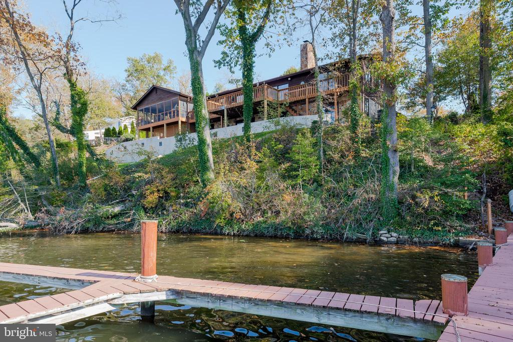 Solitude on the Severn.  This sought-after waterfront Severna Park location boasts a 3/4 bedroom, 3 bath, open floor plan with a beautiful view of deep-water Forked Creek, off the Severn River.  Enjoy a 2 car garage with workshop space, large screened-in porch and full deck, 3 connected piers with  space for 3 plus boats.  Entertaining is effortless in a bright, well appointed kitchen with and L-shaped double level island with glass cook top and double wall ovens. This eat-in kitchen has loads of space for extra guests and adjoins a family room with beautiful stone wood burning fireplace with fan assisted circulation for efficiency.  The master suite includes a whirlpool tub and separate shower and the second bathroom has a bathtub shower and sauna.  An office could be used as a fourth bedroom.  The walk-out, lower-level, has a beautiful creek view and its own bedroom and full bath, bar and game room. Perfect space for a potential in-law or au-pair quarters. If you favor a ranch-style  waterfront home in Severna Park with 160 ft shoreline on deep water, with loads of light, ample parking and a large yard for a garden, you won't want to miss seeing this home!